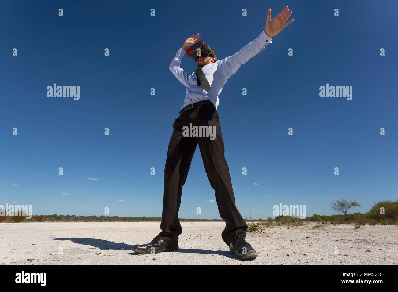 A young businessman wearing virtual reality goggles in a barren landscape, business concepts. - Stock Image