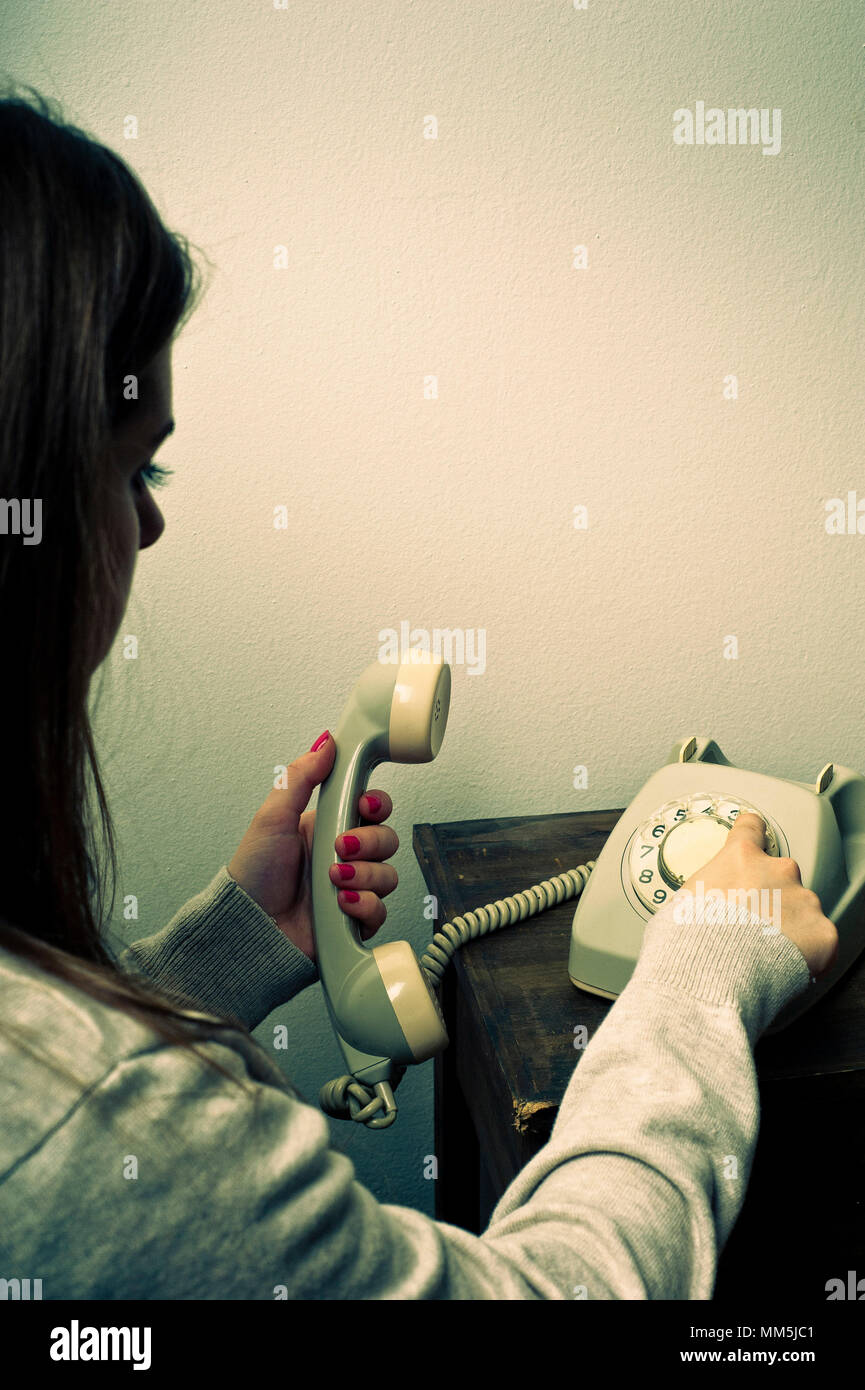 young woman dialing on a dial tone telephone - Stock Image
