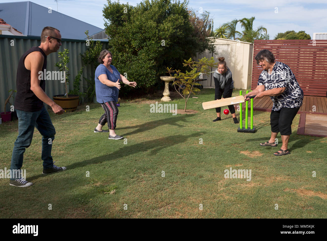 A family playing cricket in the back yard. - Stock Image