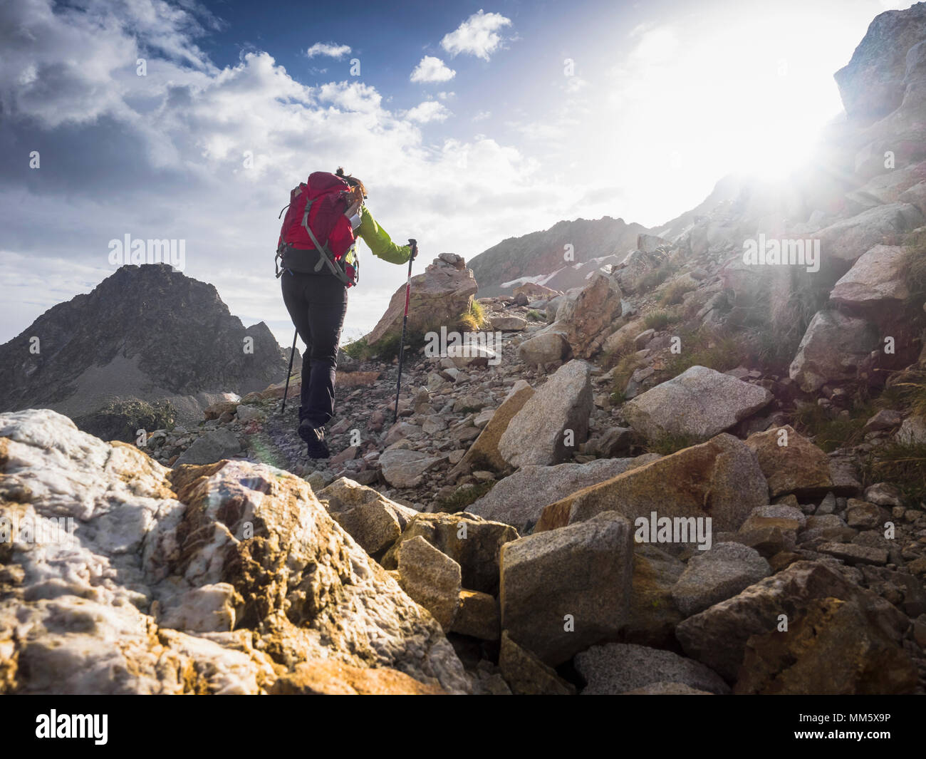 Woman hiking in the High Pyrenees ascending to mount Vignemale, Cauterets, France - Stock Image