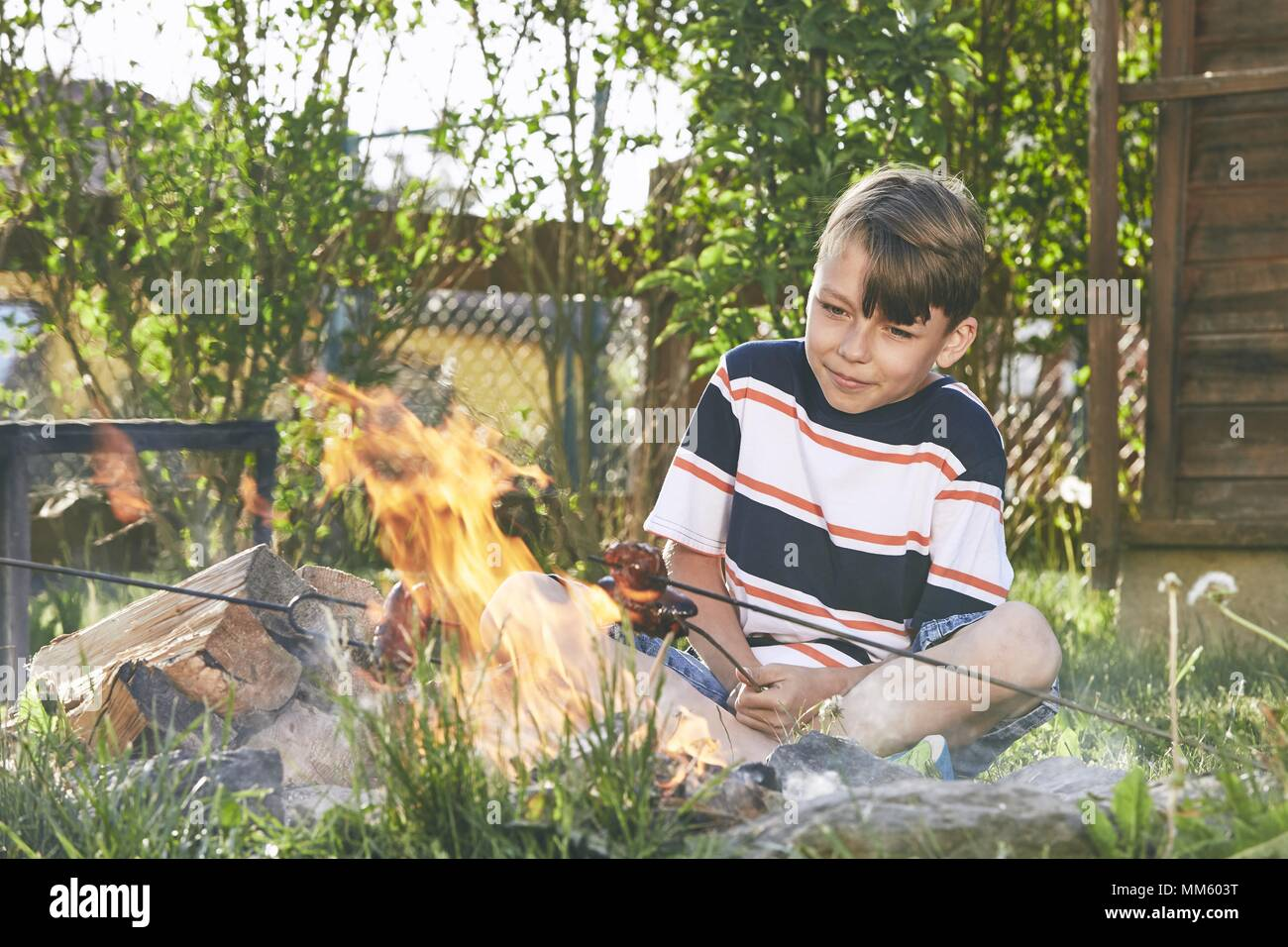 Children enjoy campfire. Boy toasting sausages on the garden. - Stock Image