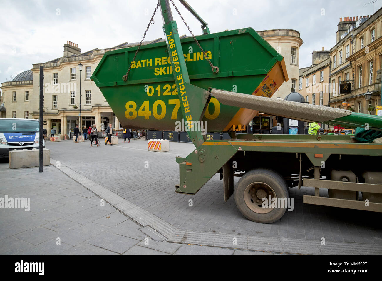 recycling skip being delivered by lorry in the city centre of Bath England UK - Stock Image