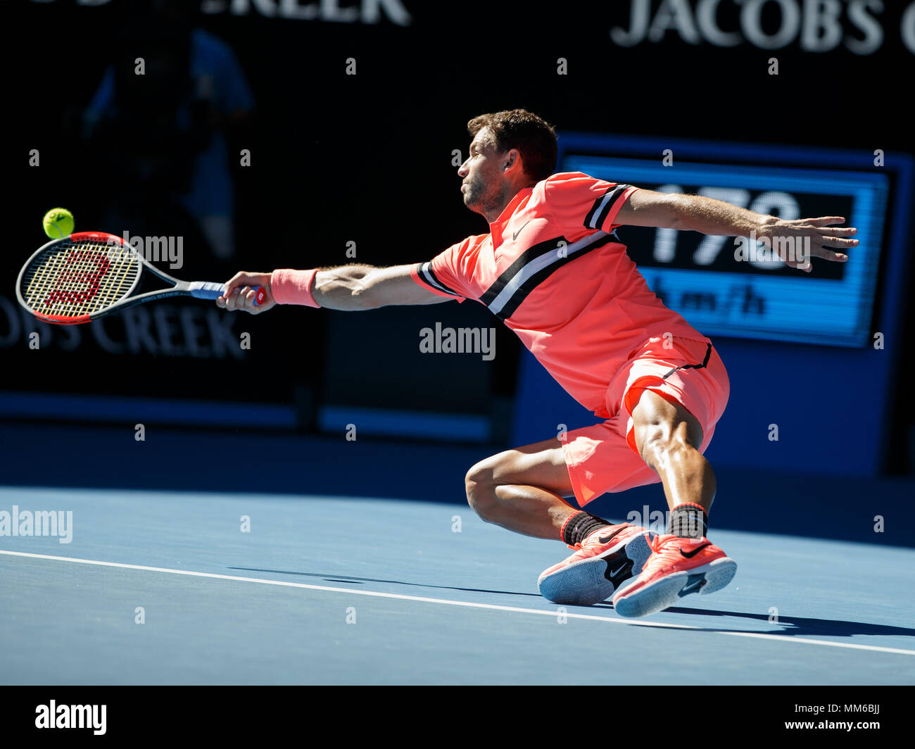 Bulgarian tennis player Grigor Dimitrov playing forehand shot  while falling, Australian Open 2018 Tennis Tournament, Melbourne Park, Melbourne, Victo - Stock Image