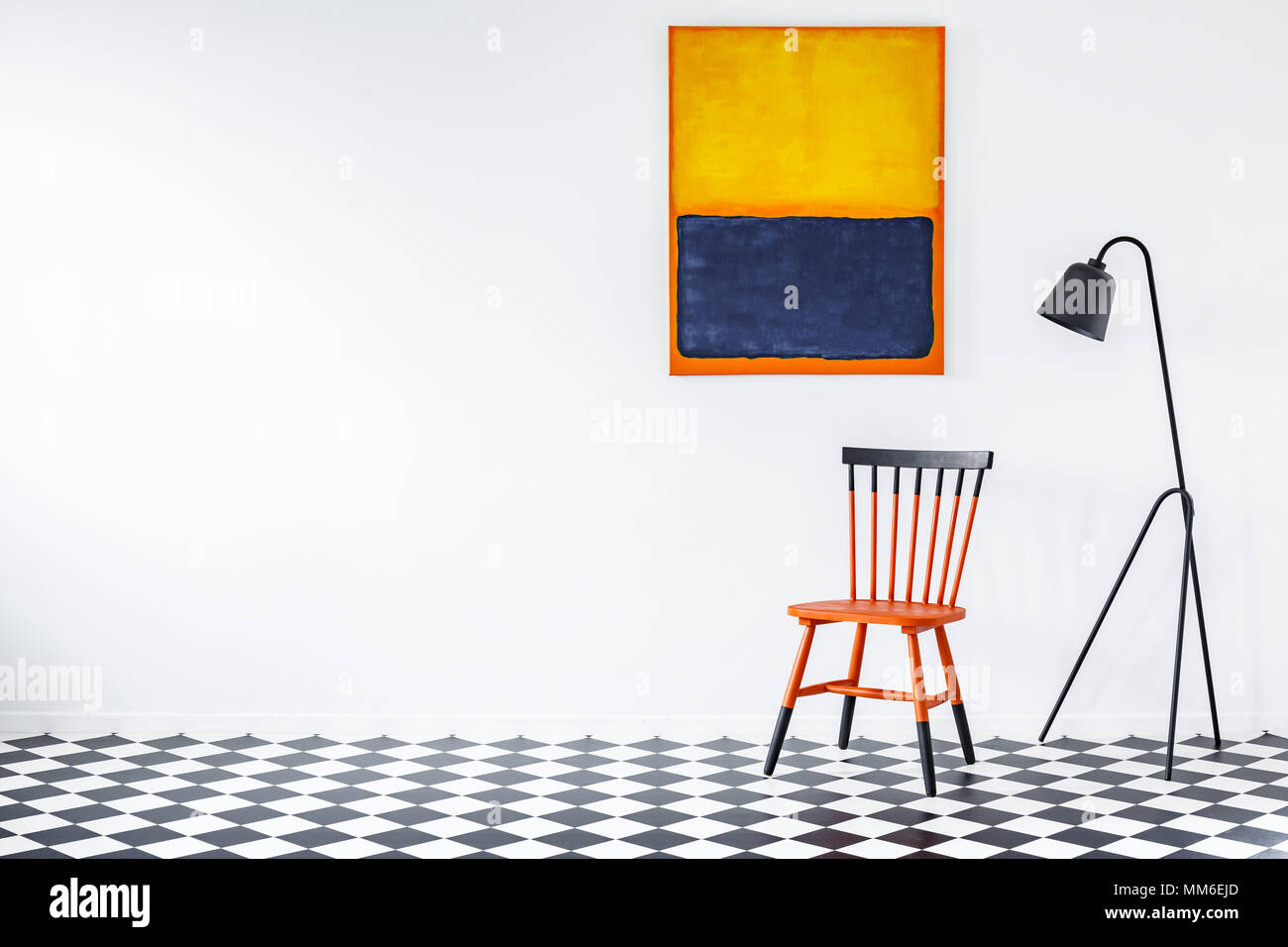 Black Lamp Next To Duocolor Chair On Checkerboard Wall In Living