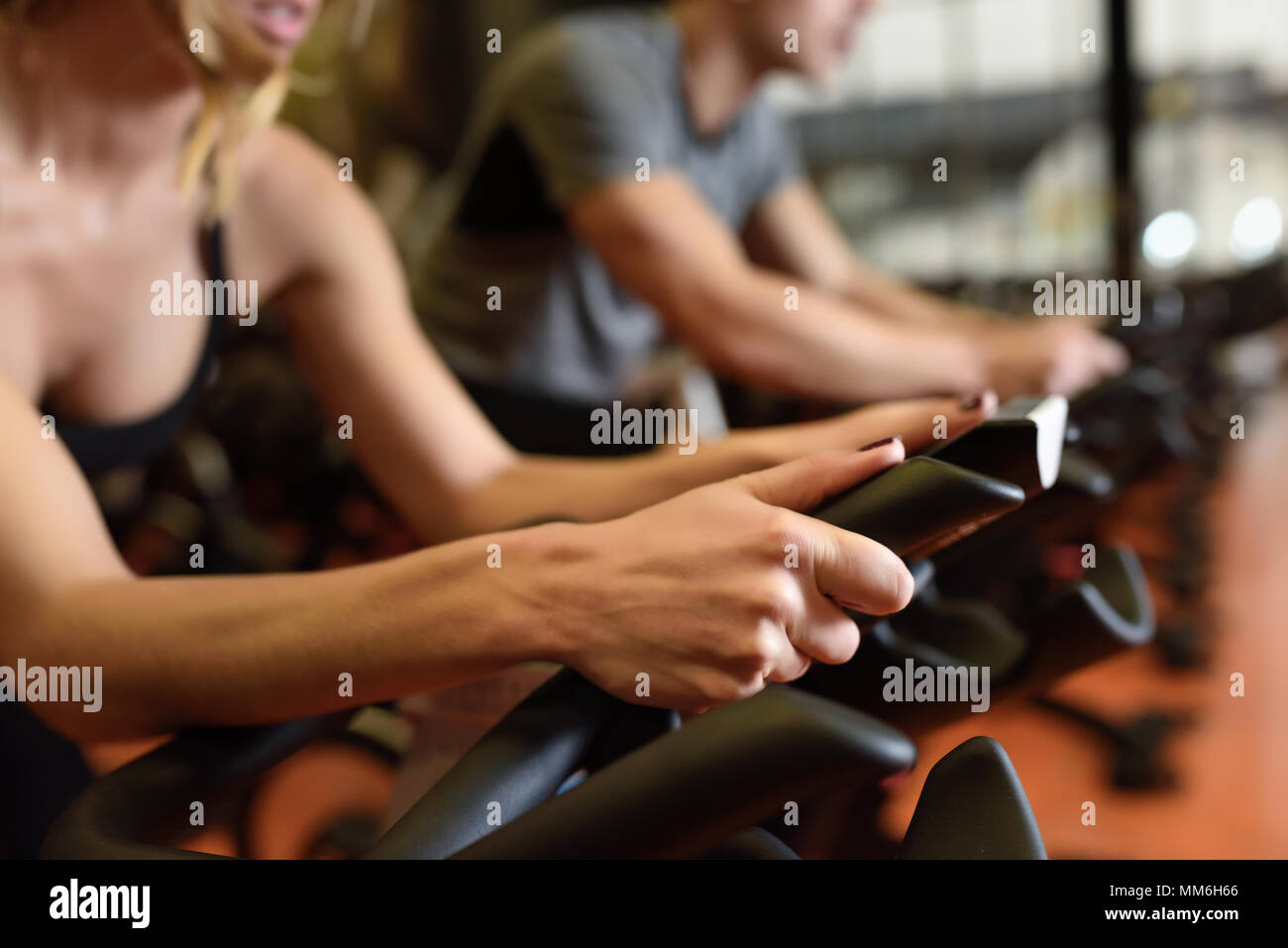 Two people biking in the gym, exercising legs doing cardio workout cycling bikes. Couple in a spinning class wearing sportswear. - Stock Image