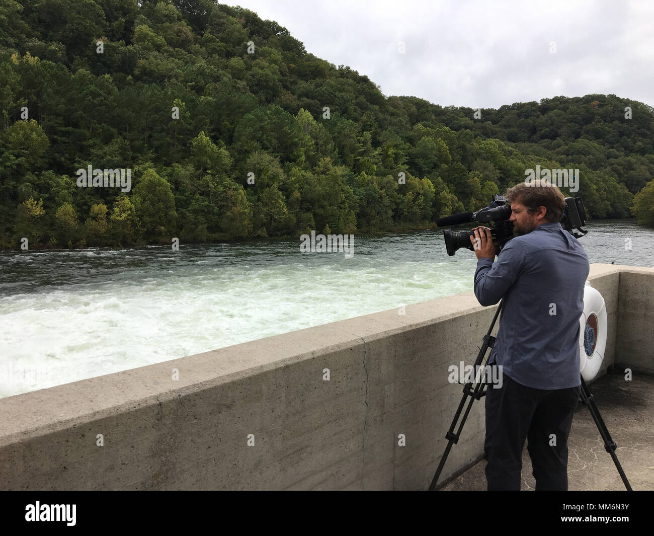 Paul Mojonnier, Tennessee Crossroads videographer, shoots footage Sept. 11, 2017 of Dale Hollow Dam's tailwater in Celina, Tenn., for an upcoming episode in early 2018 for a feature as part of the dam's 75th anniversary, also in 2018. The program airs on Nashville Public Television. (USACE photo by Sondra Carmen) - Stock Image