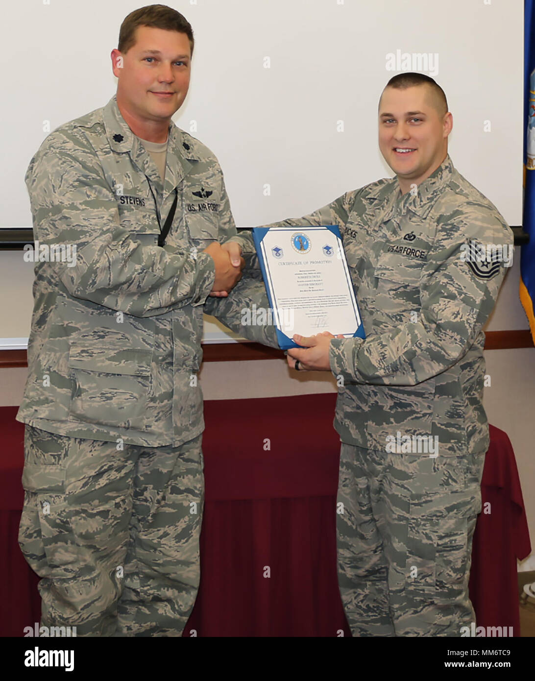 New York Air National Guard Master Sgt. Robert Dicks, right, was promoted on Sept. 13. Lt. Col. Joseph Stevens, an assistant flight commander with the 224th Air Defense Squadron, served as the promotion officer and is pictured handing Master Sgt. Dicks his promotion certificate. New York Air National Guard promotions recognize an individual's capability for additional responsibility and leadership. - Stock Image