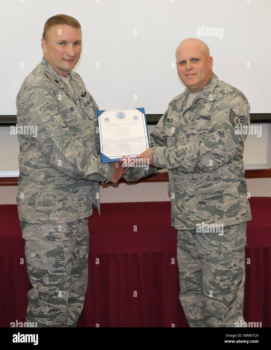 New York Air National Guard Master Sgt. Corey Reynolds, right, was promoted on Sept. 13. Maj. Michael Kidd, an assistant flight commander with the 224th Air Defense Squadron, served as the promotion officer and is pictured handing Master Sgt. Reynolds his promotion certificate. New York Air National Guard promotions recognize an individual's capability for additional responsibility and leadership. - Stock Image