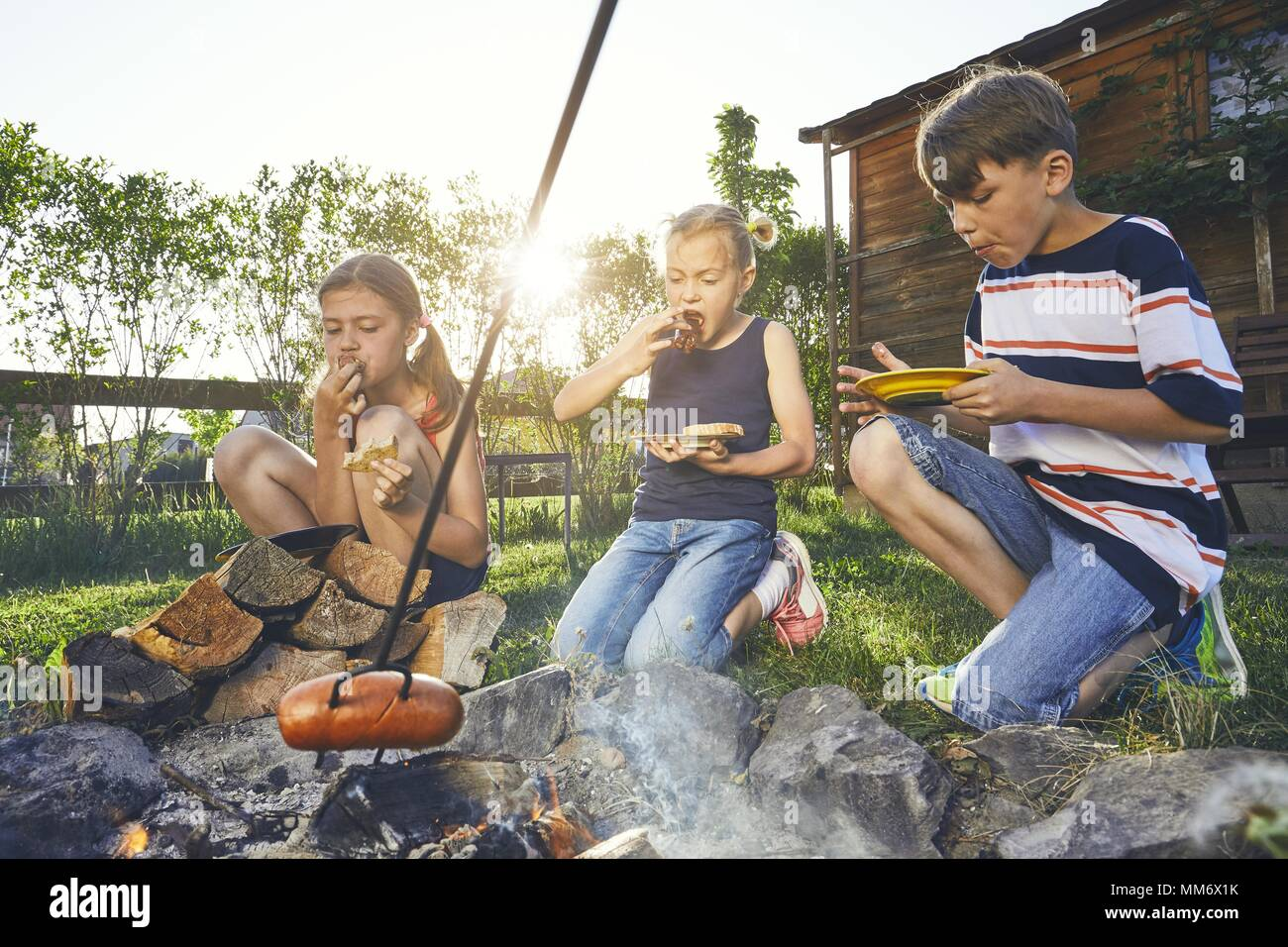 Children enjoy campfire. Siblings (family) toasting sausages on the garden at sunset. - Stock Image