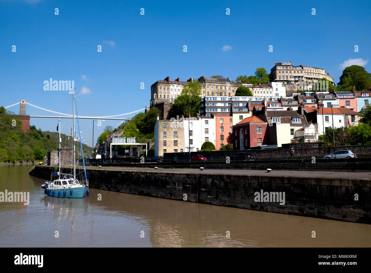 Passing underneath Clifton Suspension Bridge, a blue sailing boat motors past the Clifton and Hotwells residential streets towards Bristol docks. - Stock Image