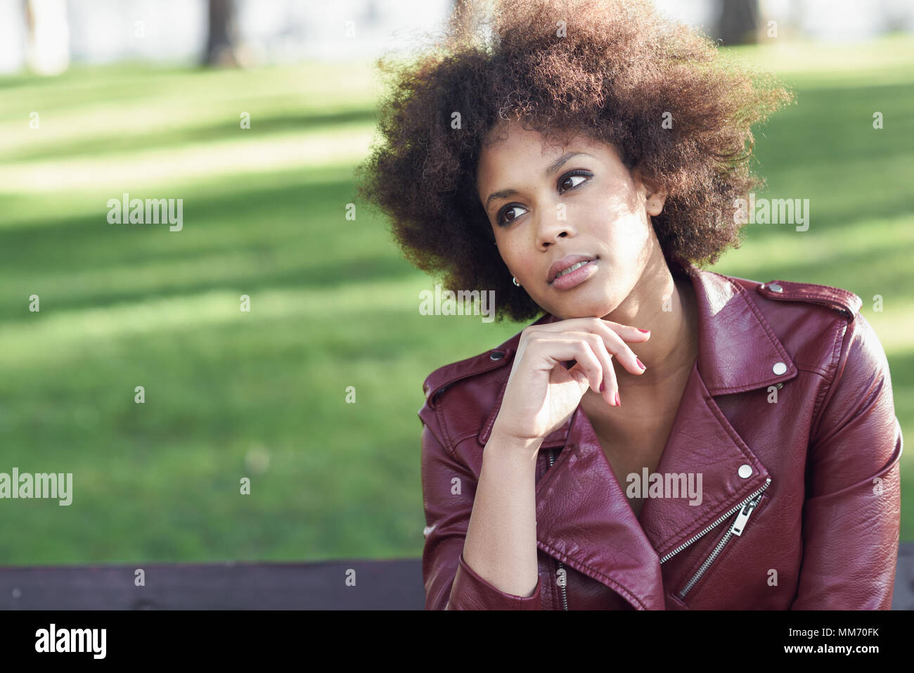Young Black Female With Afro Hairstyle Sitting In A Bench In An