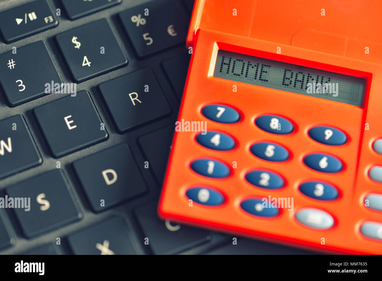 Home bank written on the display of the digipass over computer keyboard. Online banking transaction concept - Stock Image