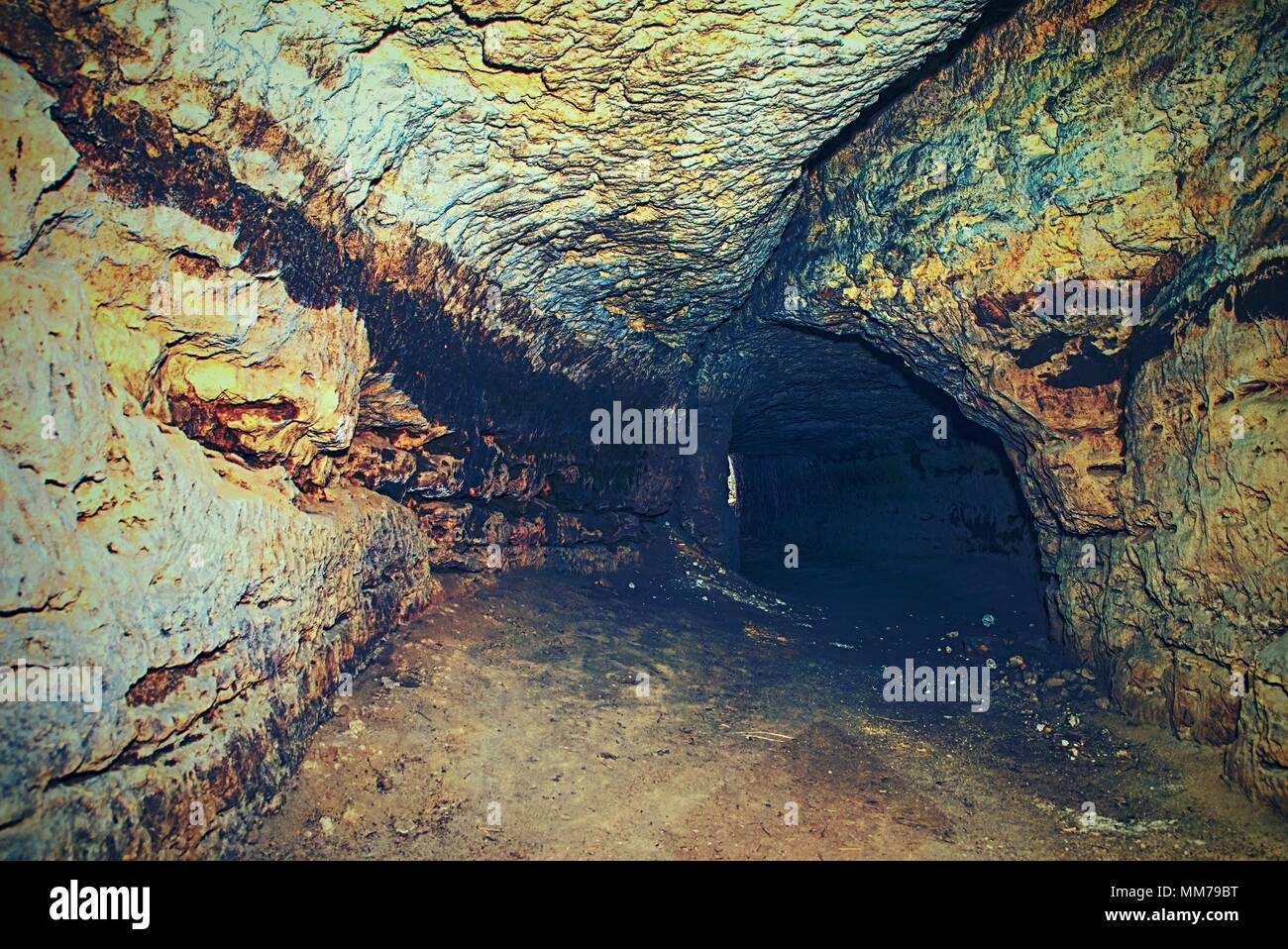 Bastion passage under city. Old catacombs built in orange sandstone rock.  The underground passages built by men for the defense during the war - Stock Image