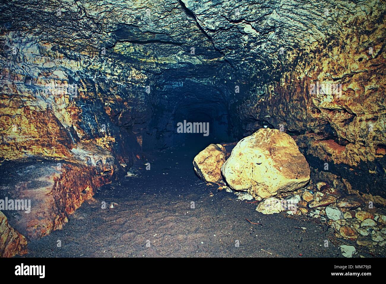 View into an empty medieval catacomb. Tunnel excavated in orange sandstone rock with sand and stones on the floor. - Stock Image