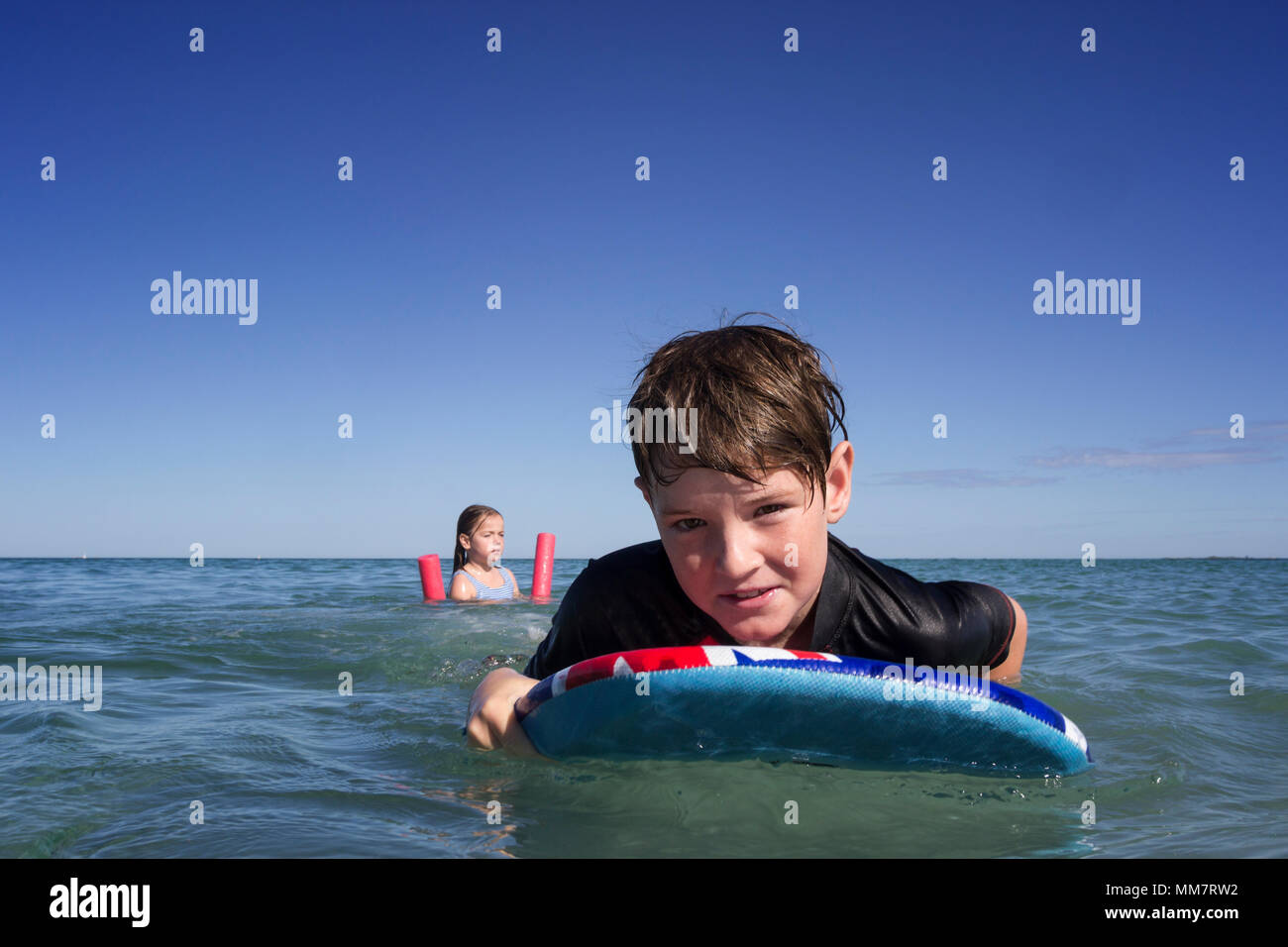 Two kids swimming, using flotation toys. Stock Photo