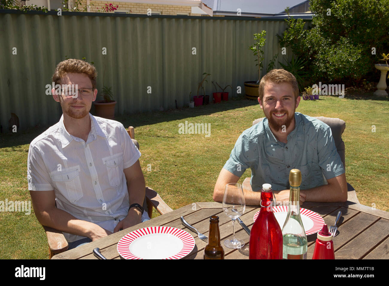Two people at a home event, waiting for food. - Stock Image
