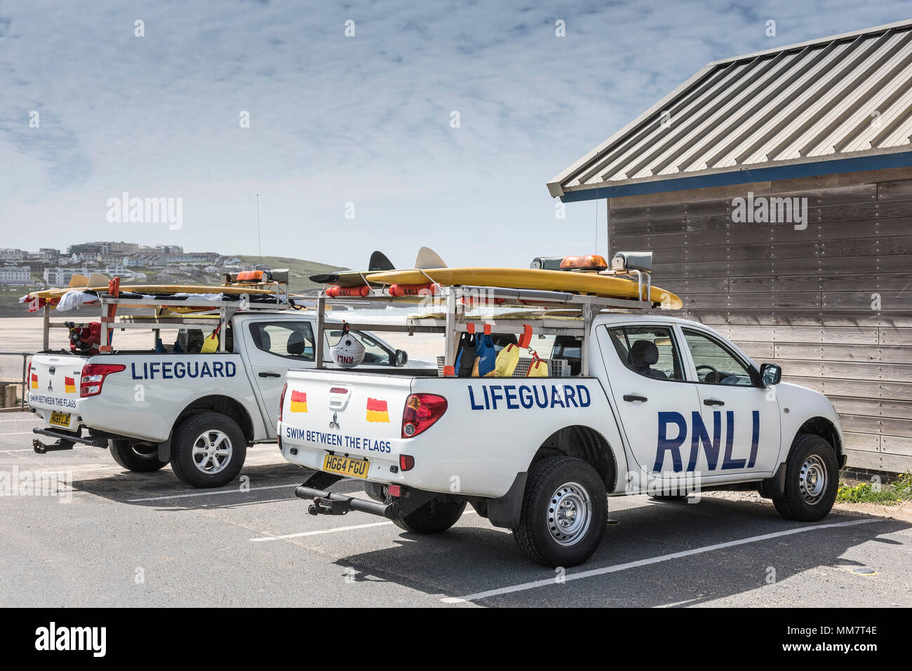 Two RNLI Lifeguard vehicles parked at Fistral in Newquay in Cornwall. - Stock Image