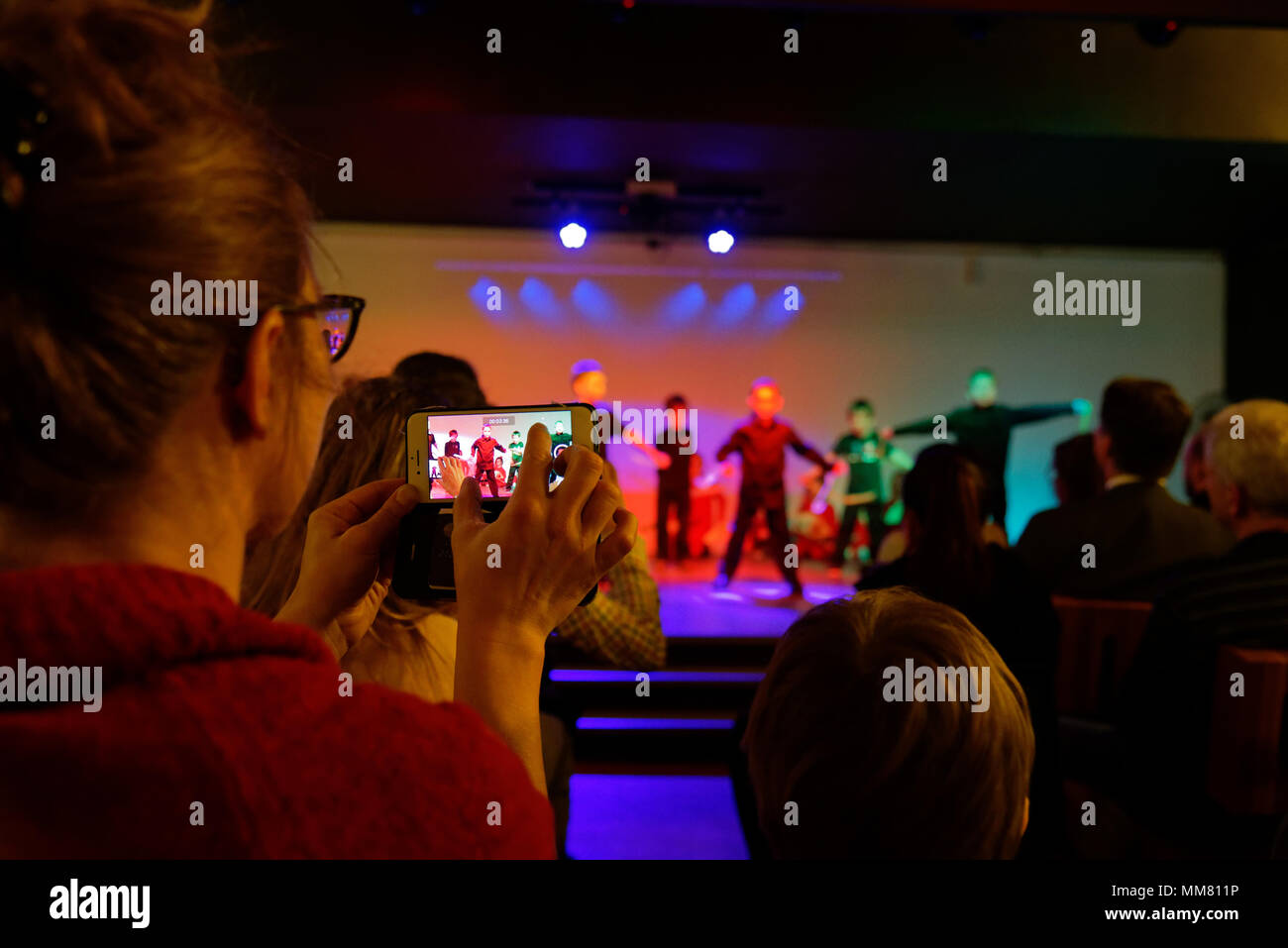 A woman filming a school concert with an iphone - Stock Image