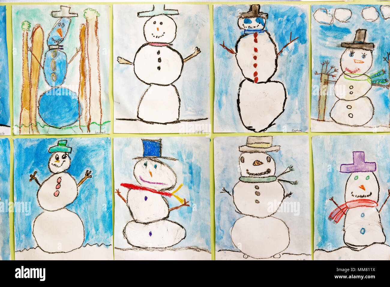 Children's art works on the wall in their school - pictures of snowmen - Stock Image