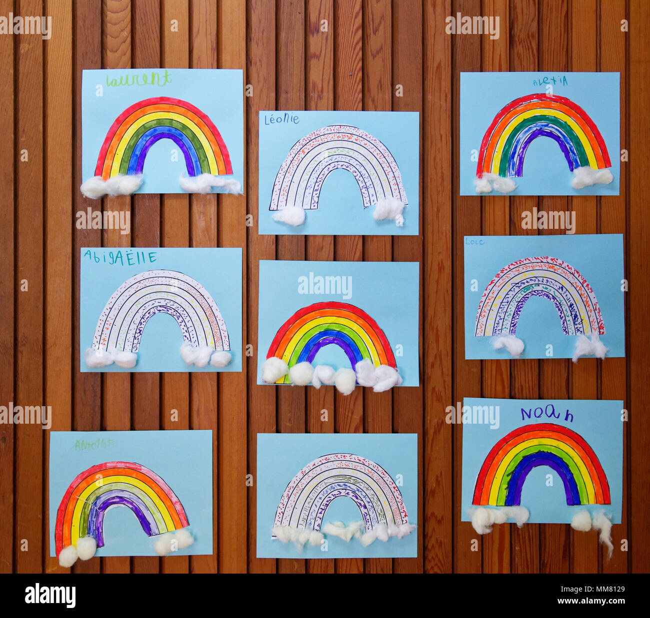 Children's art works on the wall in their school - rainbows - Stock Image