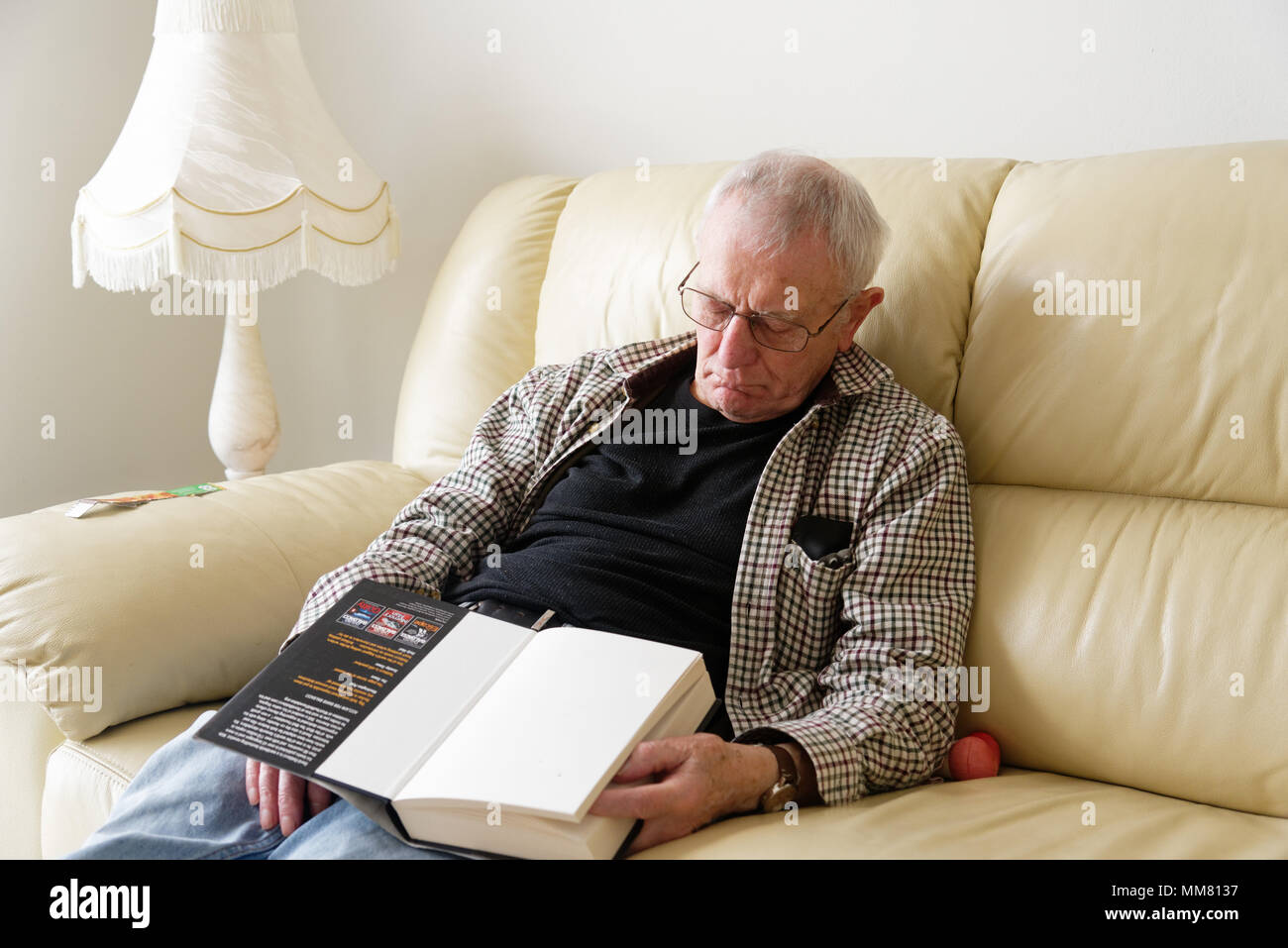 Anolder man fallen asleep on the sofa while reading a book - Stock Image