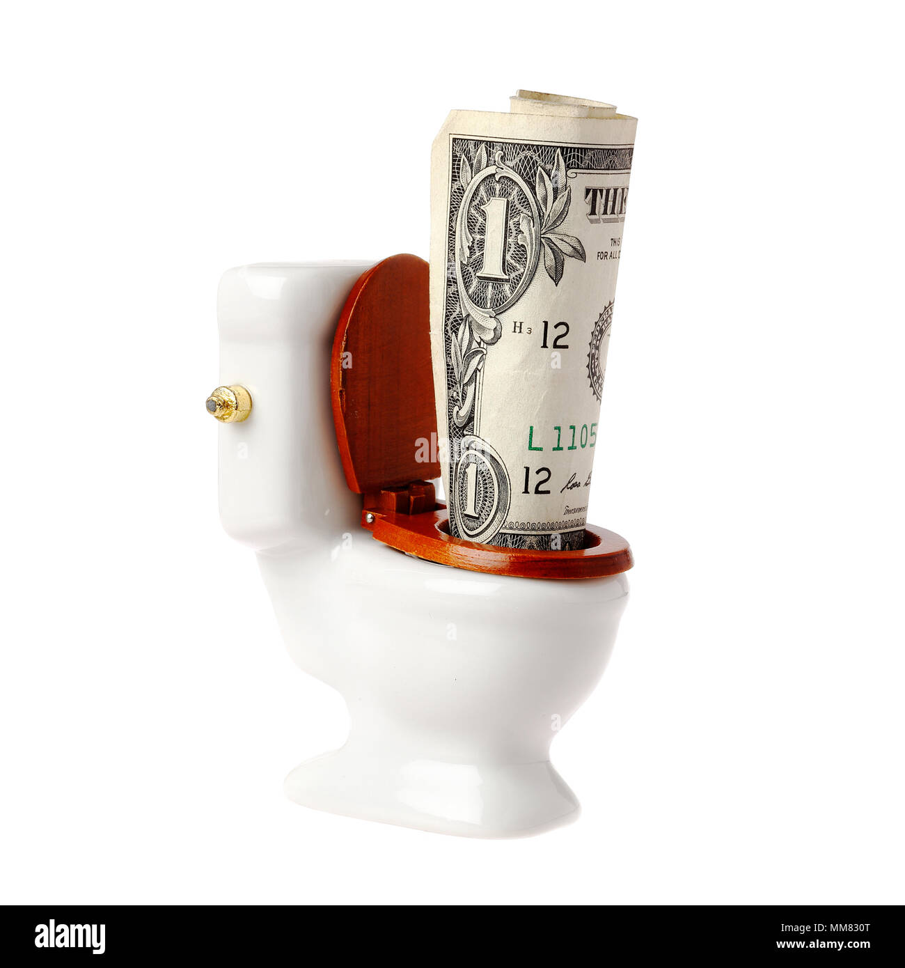 One US dollar banknote in a miniature toilet, isolated on white background. Stock Photo