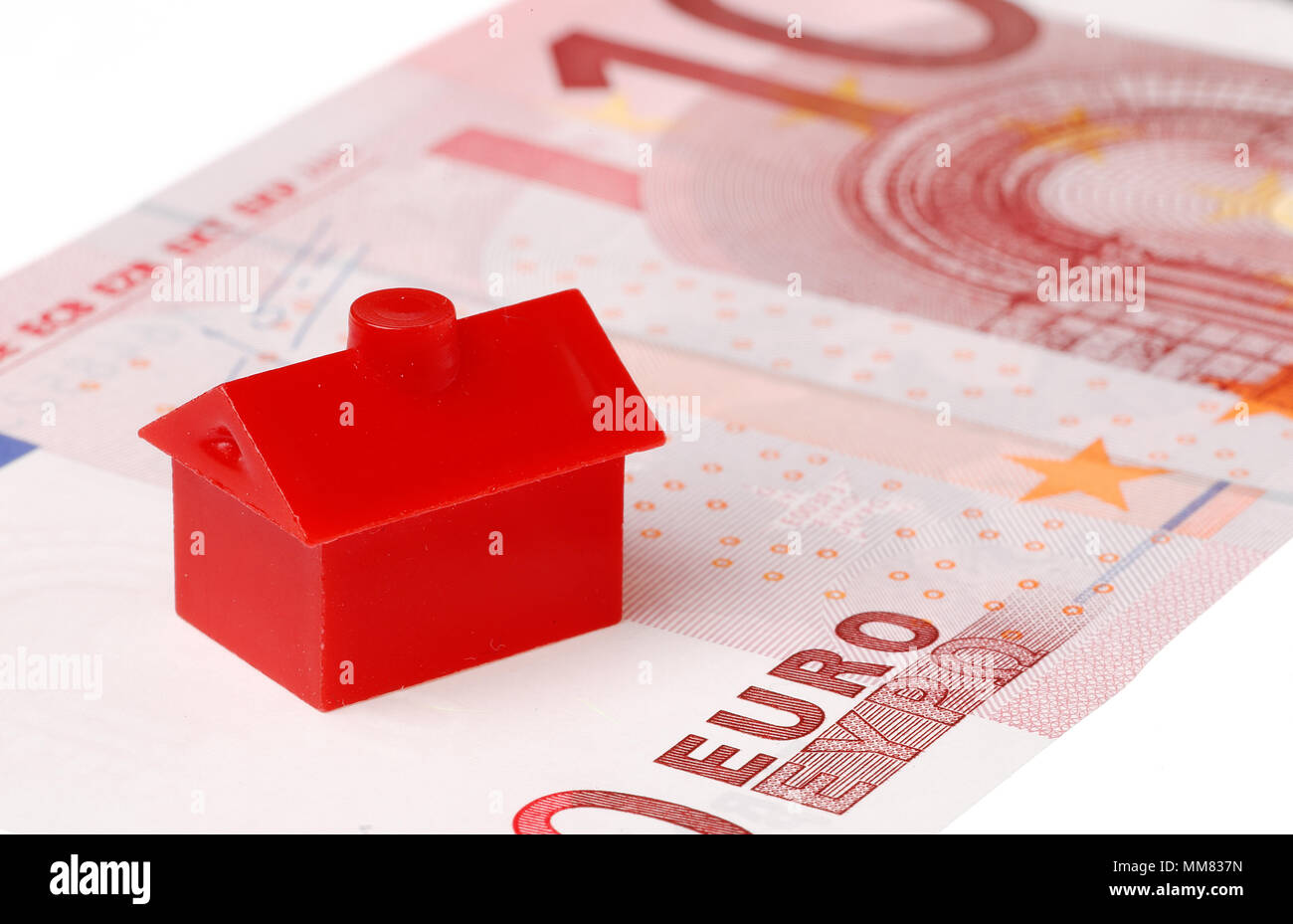 Red litle plastic house on a ten euro banknote on white background. - Stock Image
