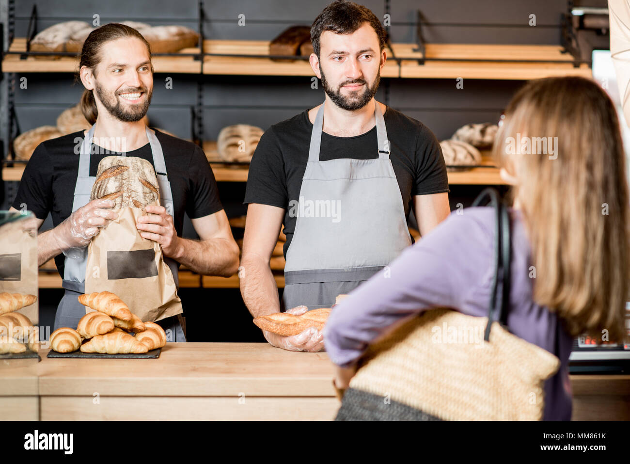 Woman buying bread in the bakery shop with man sellers Stock Photo