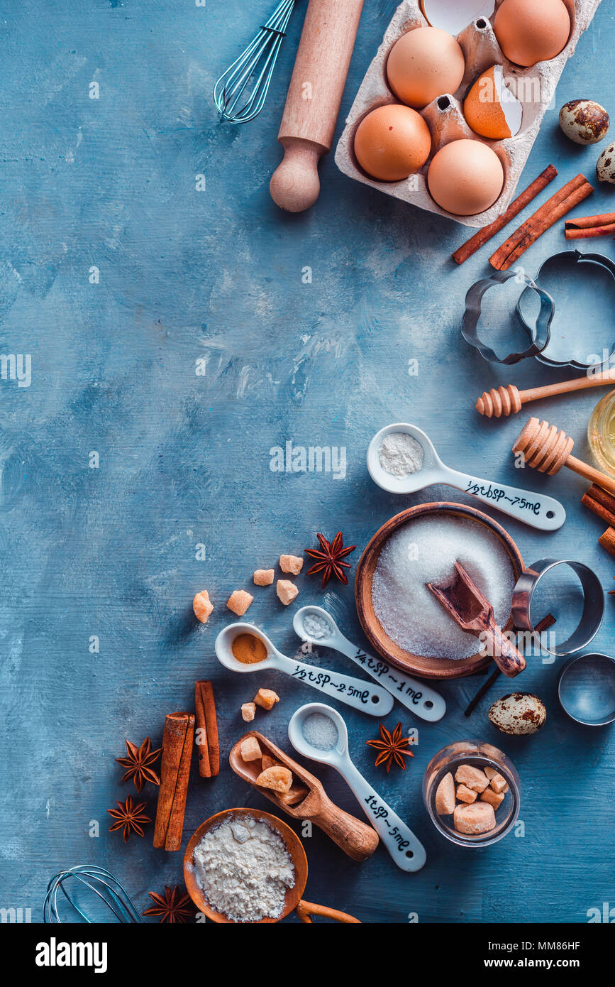 Cooking tools and ingredients from above. Baking concept with measuring spoons, wooden scoops, whisks, cookie cutters, sugar, flour, eggs and cinnamon - Stock Image