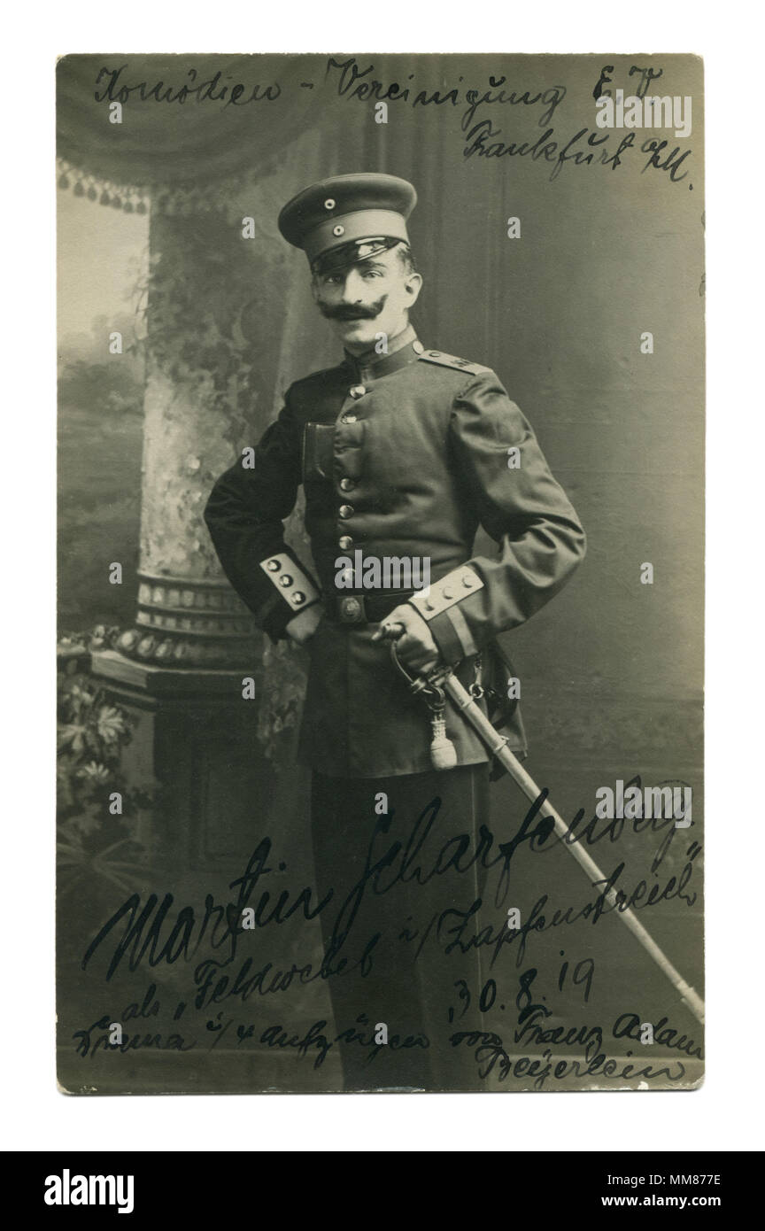 Old German photo of 1919: a man in uniform with a black mustache and a sword on his belt. The actor of drama theatre. Autograph. Military staging. - Stock Image