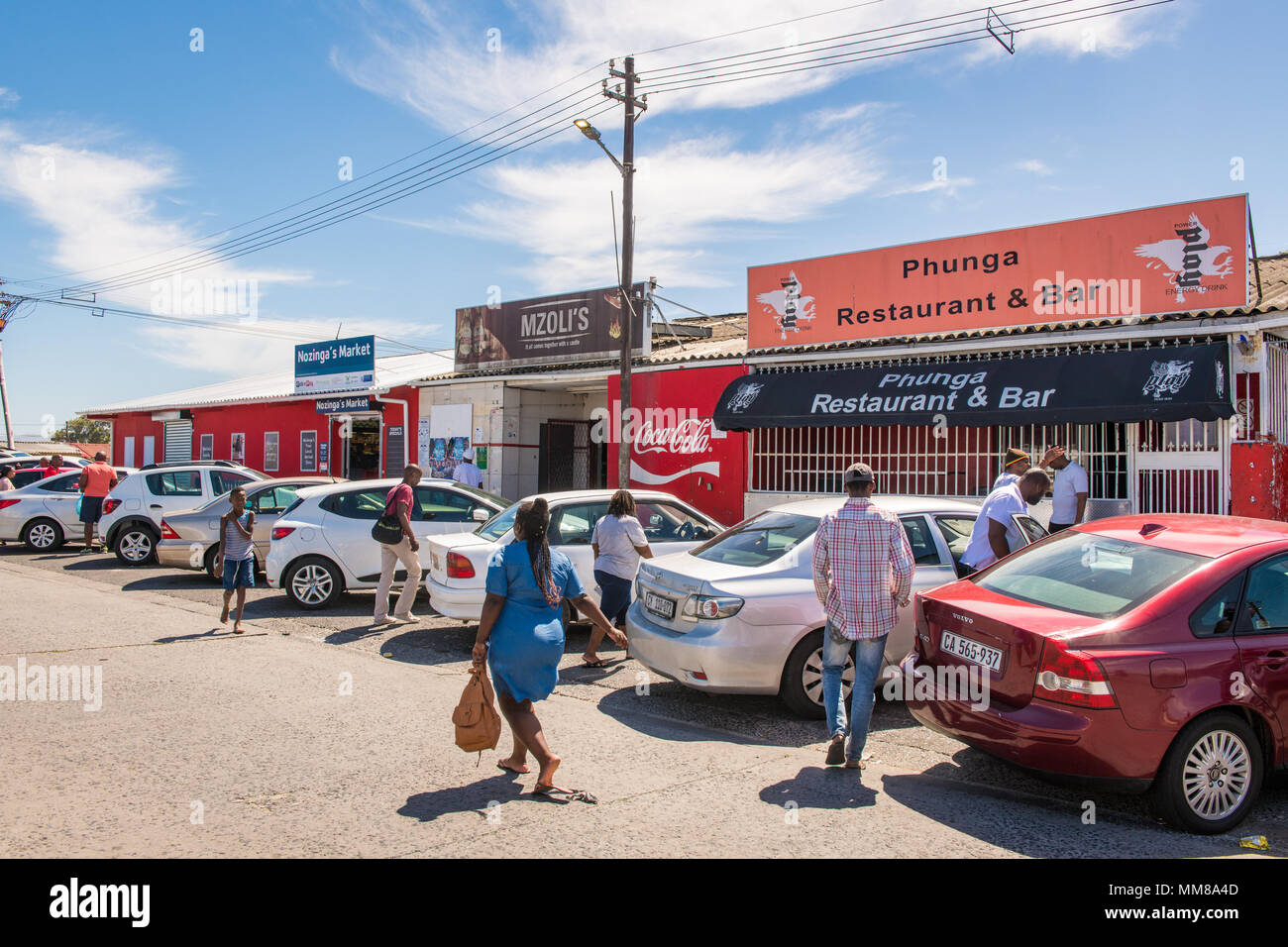A cluster of cars sits outside local businesses as people mill about in Guguletu township in Cape Town, South Africa - Stock Image