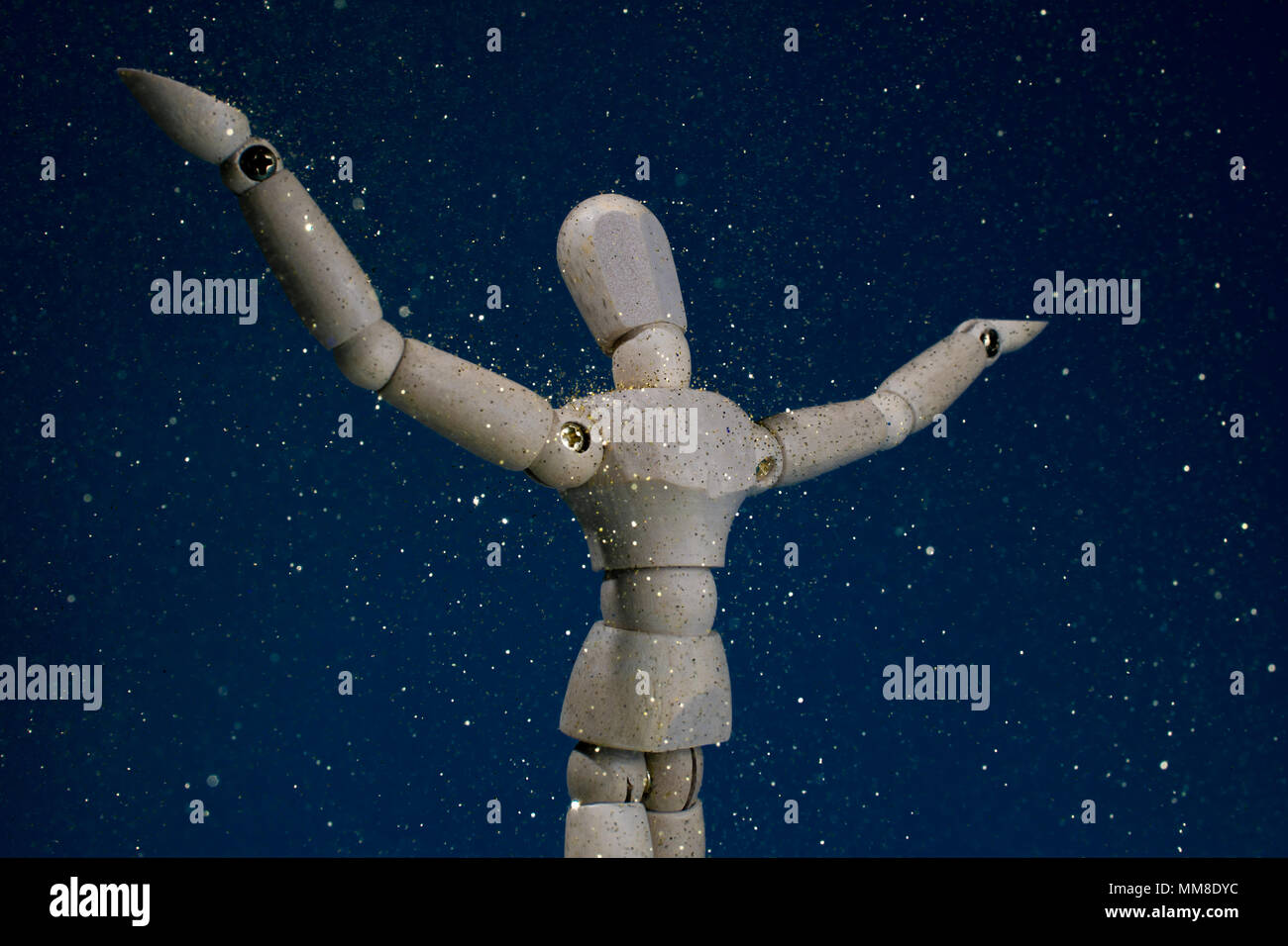 Mannequin figurine standing in gold rain with arms outstretched - Stock Image