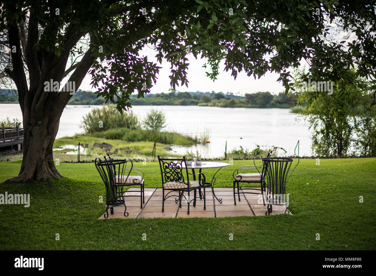 A table setup overlooks picturesque view of the Zambezi River at the Royal Livingston Hotel in Livingstone, Zambia - Stock Image