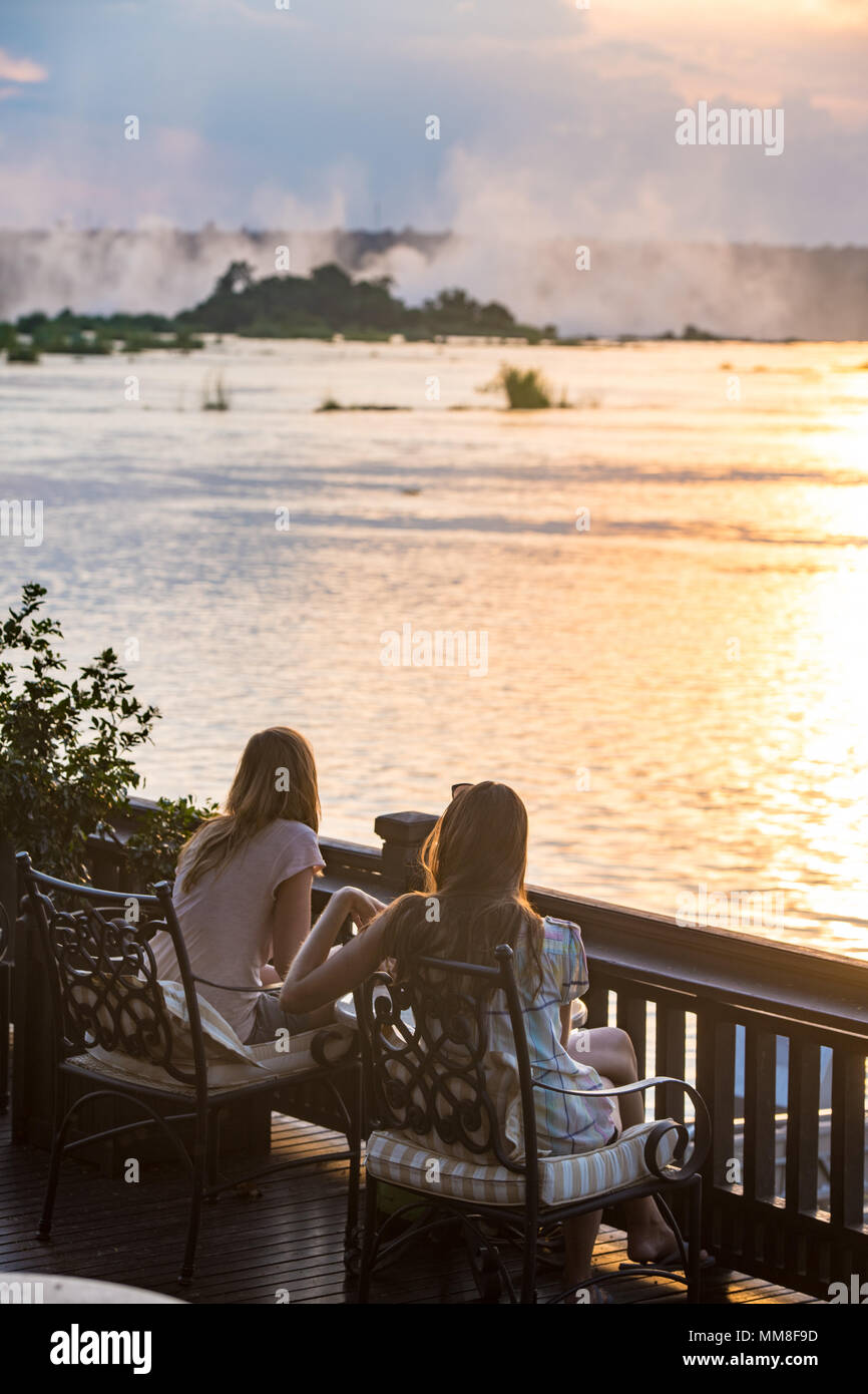 Two young women sit on the sundeck of the Royal Livingston Hotel and watch the sun set over the Zambezi River Livingstone, Zambia - Stock Image