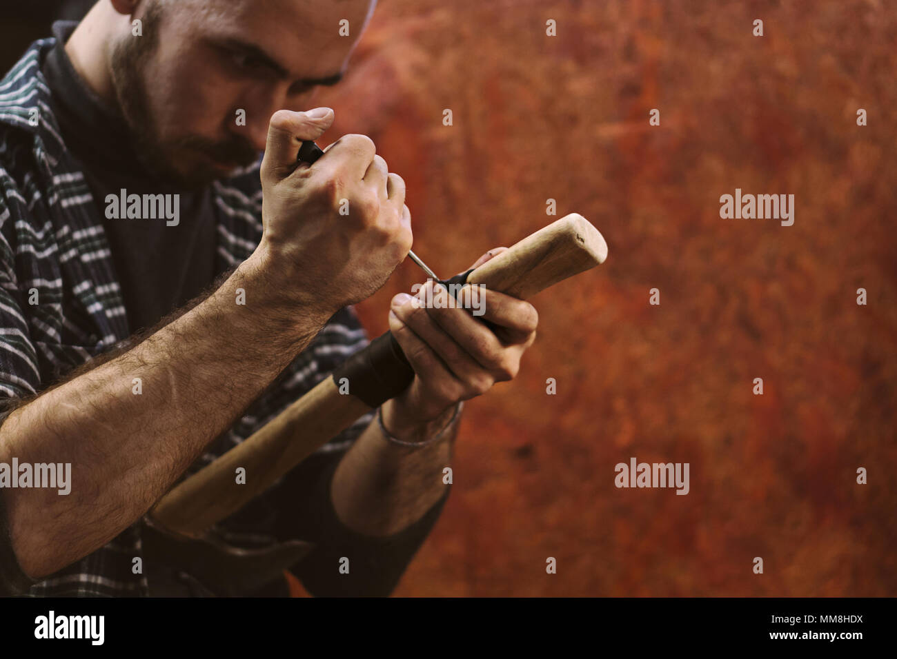 Man working in carpentry workshop. He pierces leather winding on wooden handle of ax. Men at work. Hand work. - Stock Image
