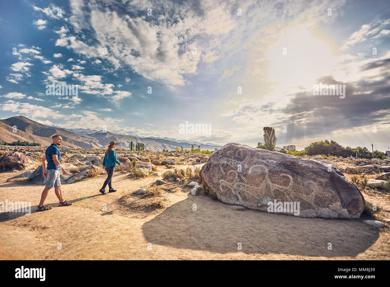 Couple in checkered shirt walking in the open air museum near stone with ancient petroglyph of goats at Kyrgyzstan - Stock Image