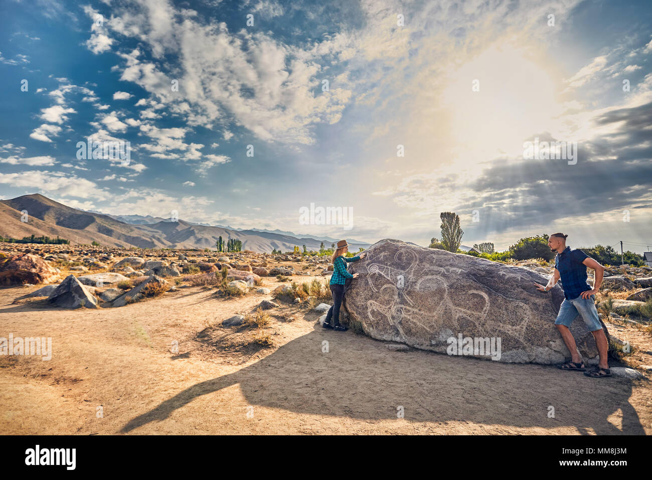 Couple in checkered shirt in the open air museum near stone with ancient petroglyph of goats at Kyrgyzstan - Stock Image