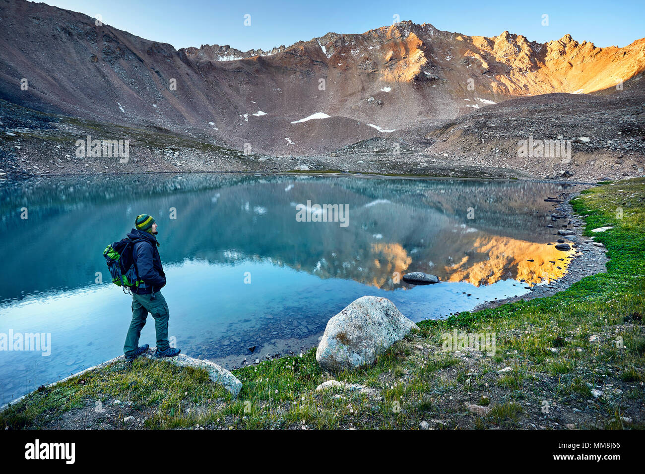 Bearded man in green hat and backpack looking at mountain lake at sunrise - Stock Image
