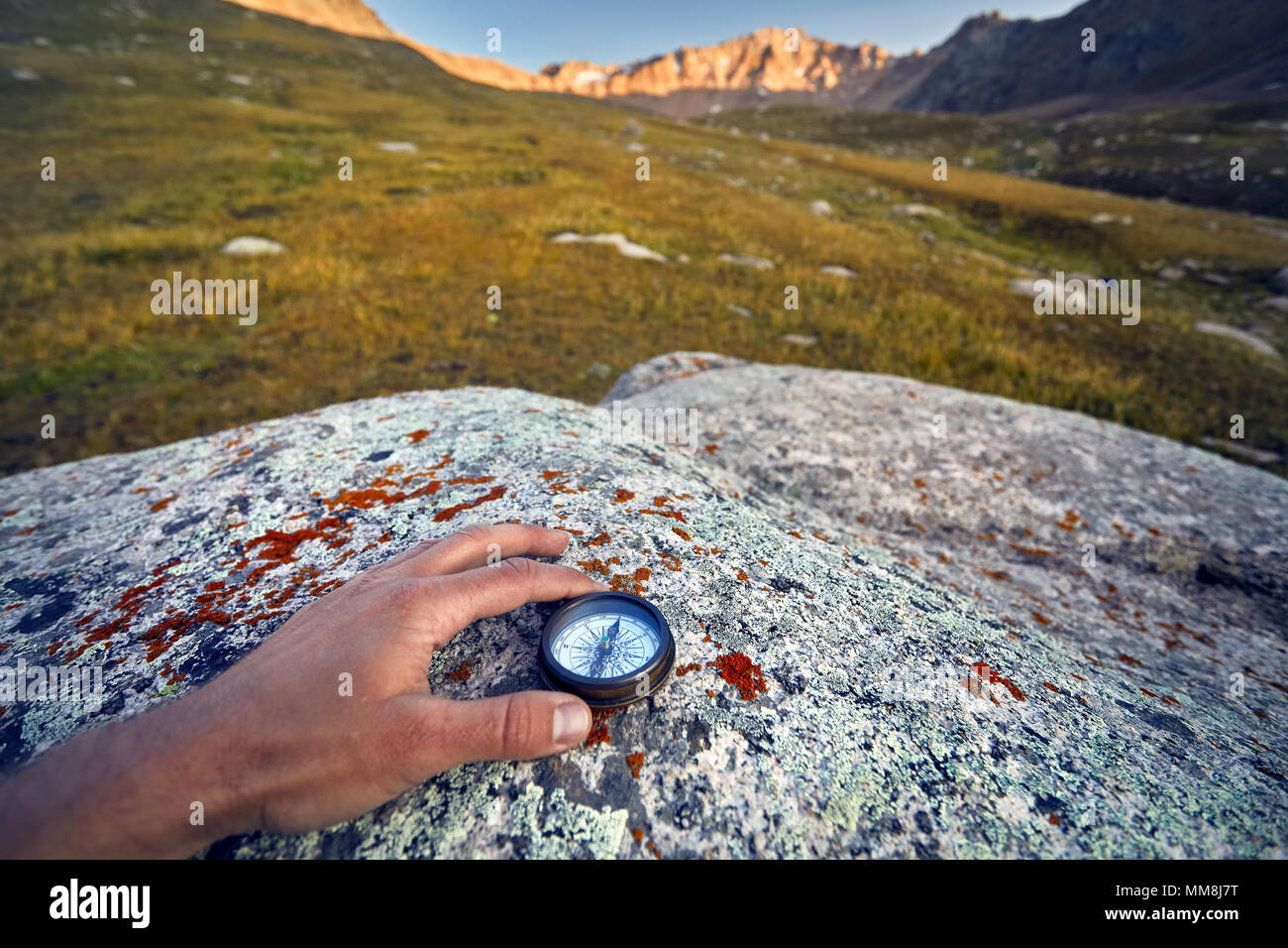 Tourist hand with vintage compass on the mountains background. Travel and adventure concept. - Stock Image