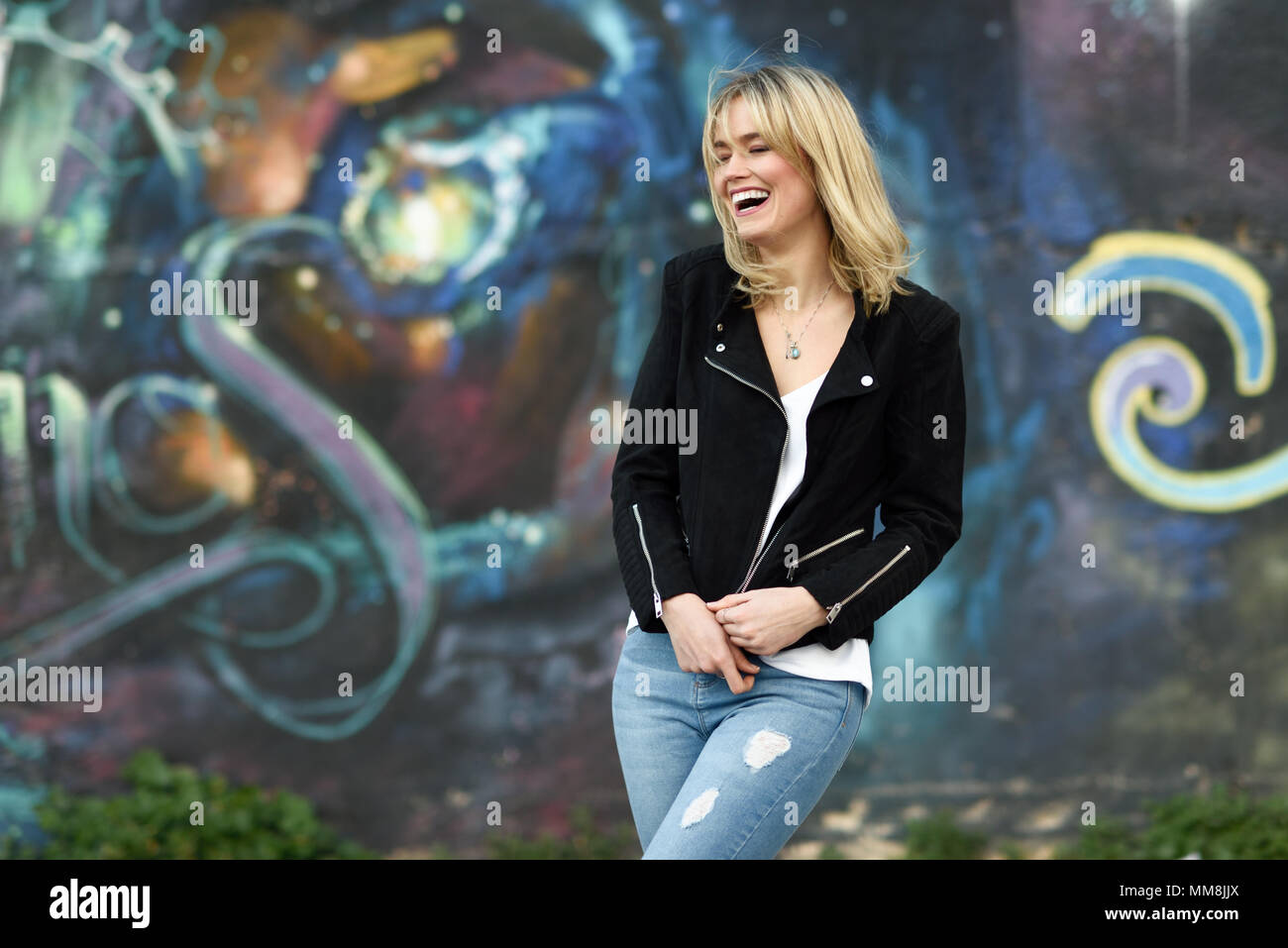52b139737a5 Funny blonde woman laughing in urban background. Young girl wearing black  zipper jacket and blue