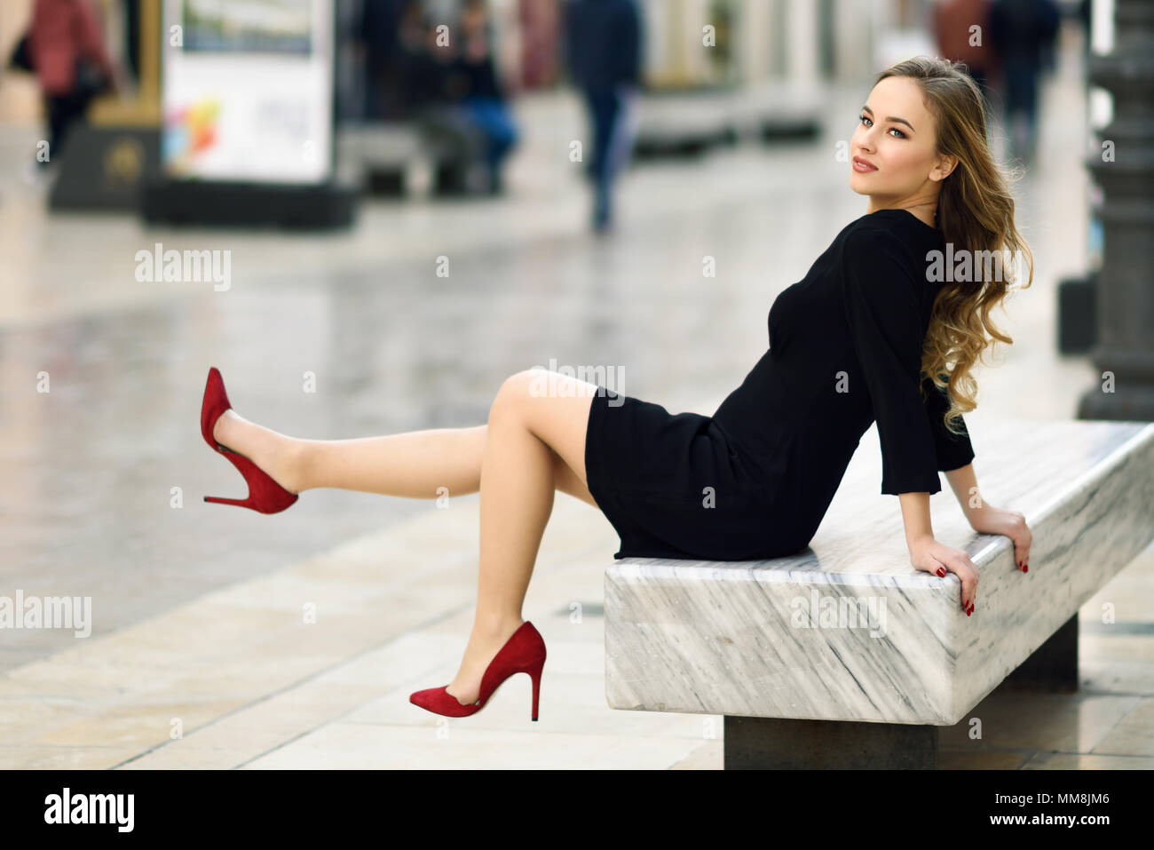 1c9a5a757 Funny blonde woman with beautiful legs in urban background. Beautiful young  girl wearing black elegant