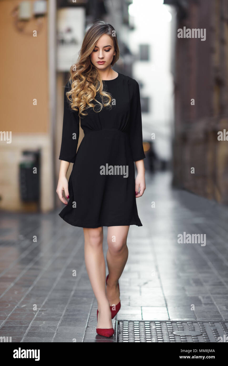 73c172d08 Blonde woman in urban background. Beautiful young girl wearing black  elegant dress and red high