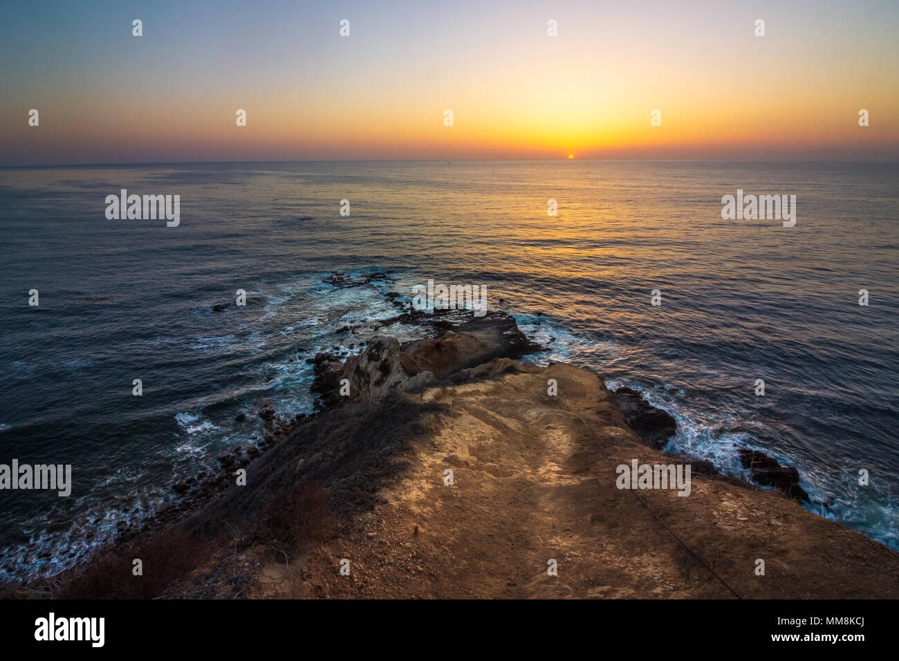 Beautiful coastal view looking down a steep hiking trail and waves crashing into Flat Rock Point as the sun sets, Palos Verdes Estates, California - Stock Image