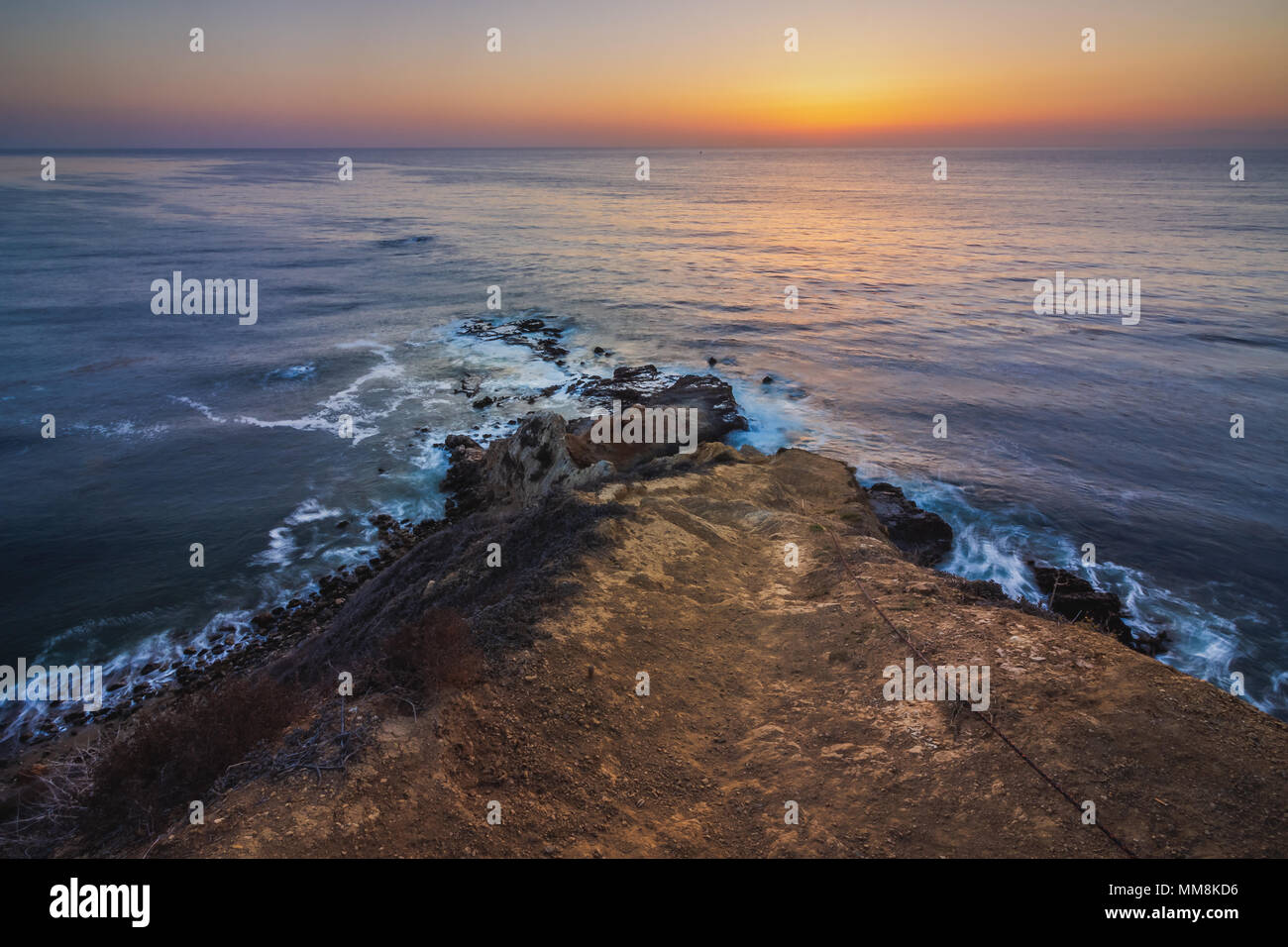 Long-exposure shot looking down a steep hiking trail at smooth waves crashing into Flat Rock Point rock formations after sunset, Palos Verdes Estates, - Stock Image