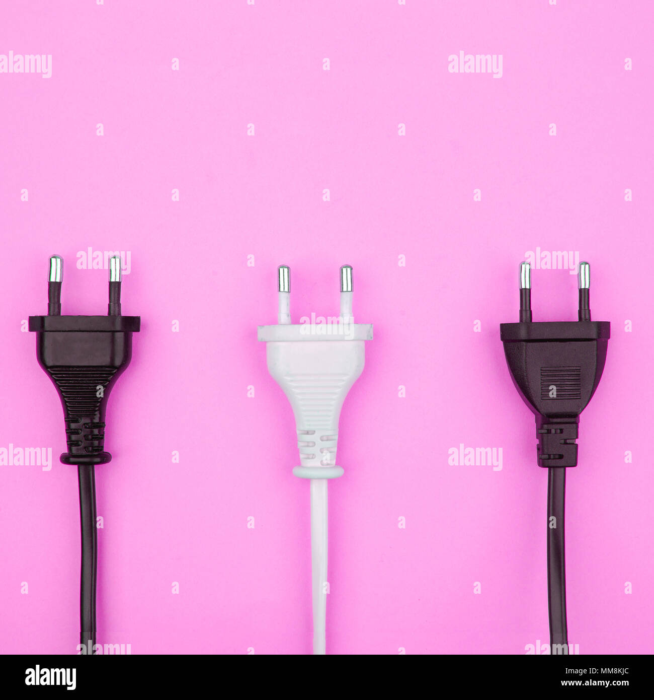 Trendy flat lay minimal concept, unplugged cord on pink background - Stock Image