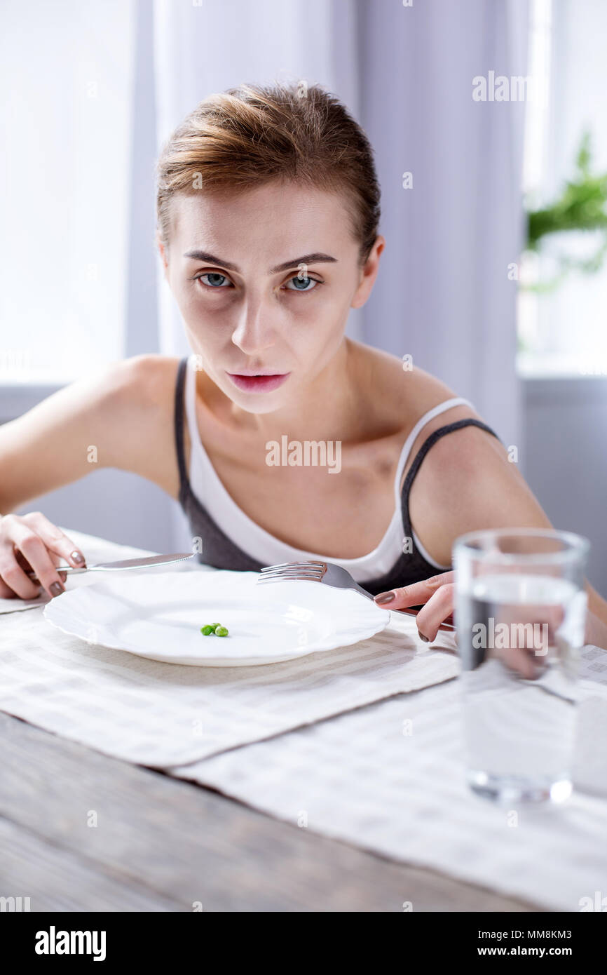 Cheerless pale woman sitting at the table - Stock Image