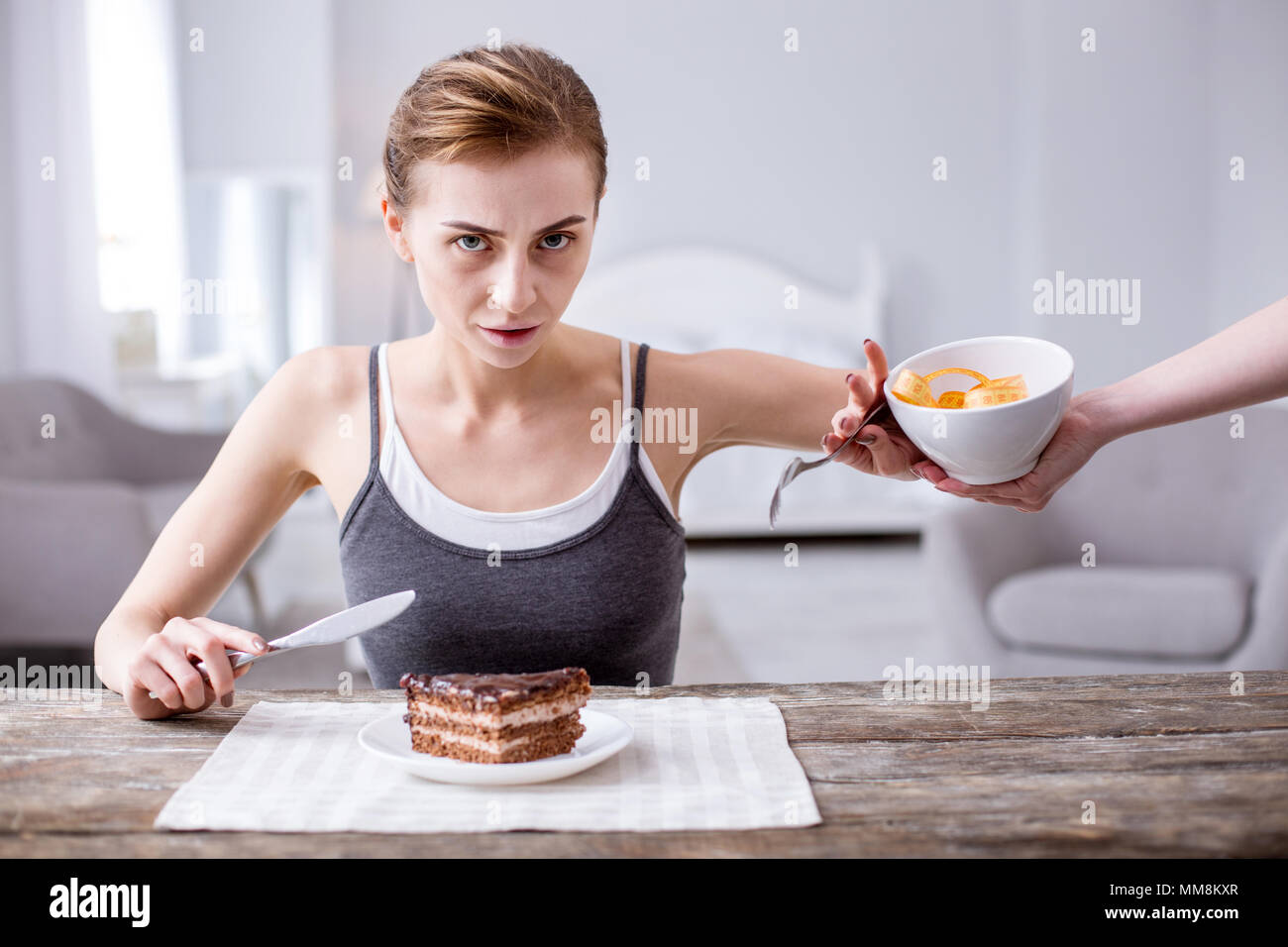 Pale young woman forgetting her diet - Stock Image