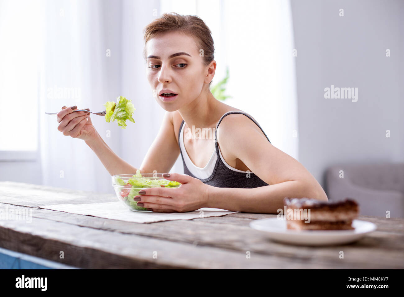 Depressed hungry woman looking at the cake - Stock Image