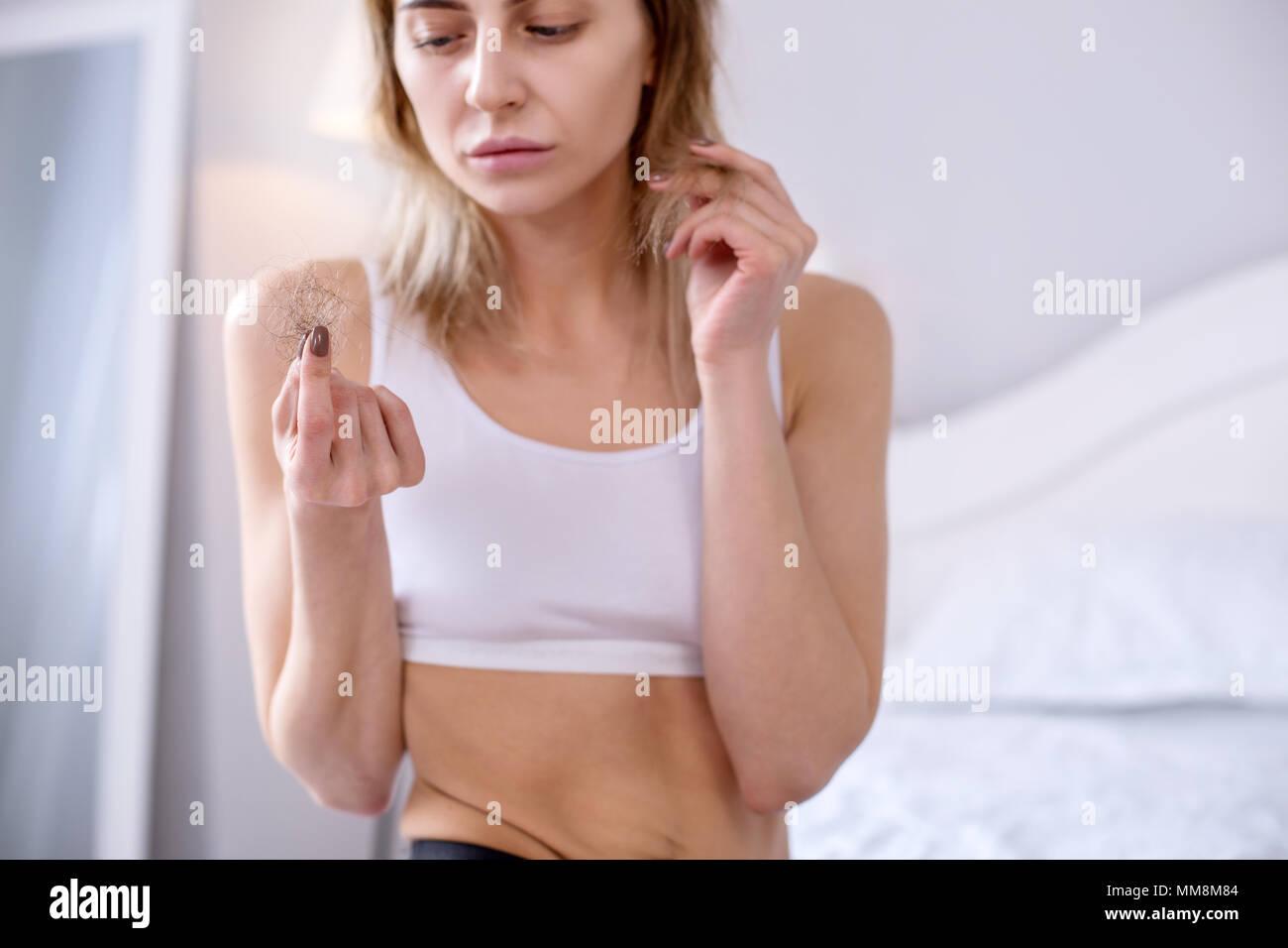 Sad depressed woman sitting at home - Stock Image