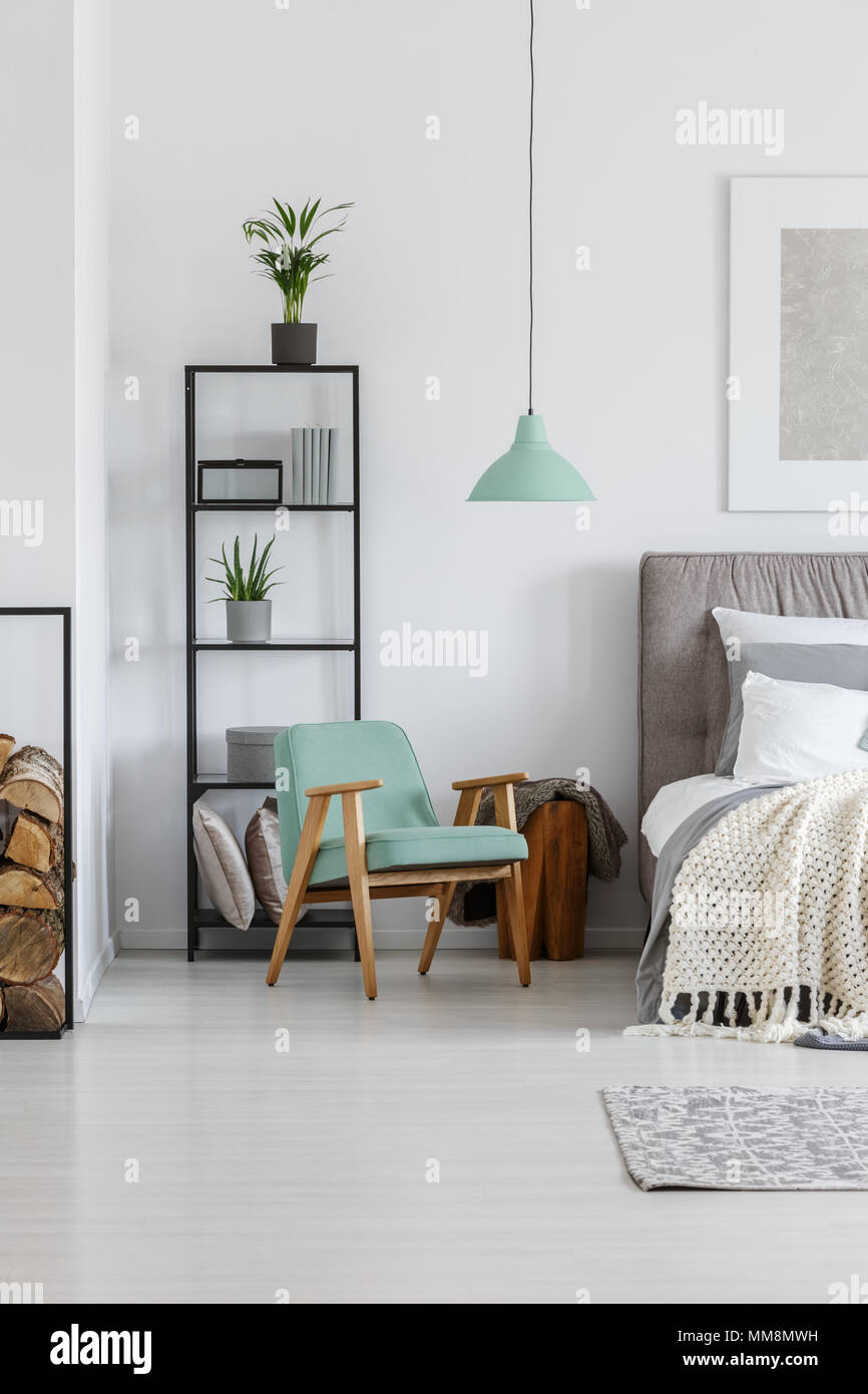 Small mint lampshade hanging above comfy wooden chair in bedroom - Stock Image